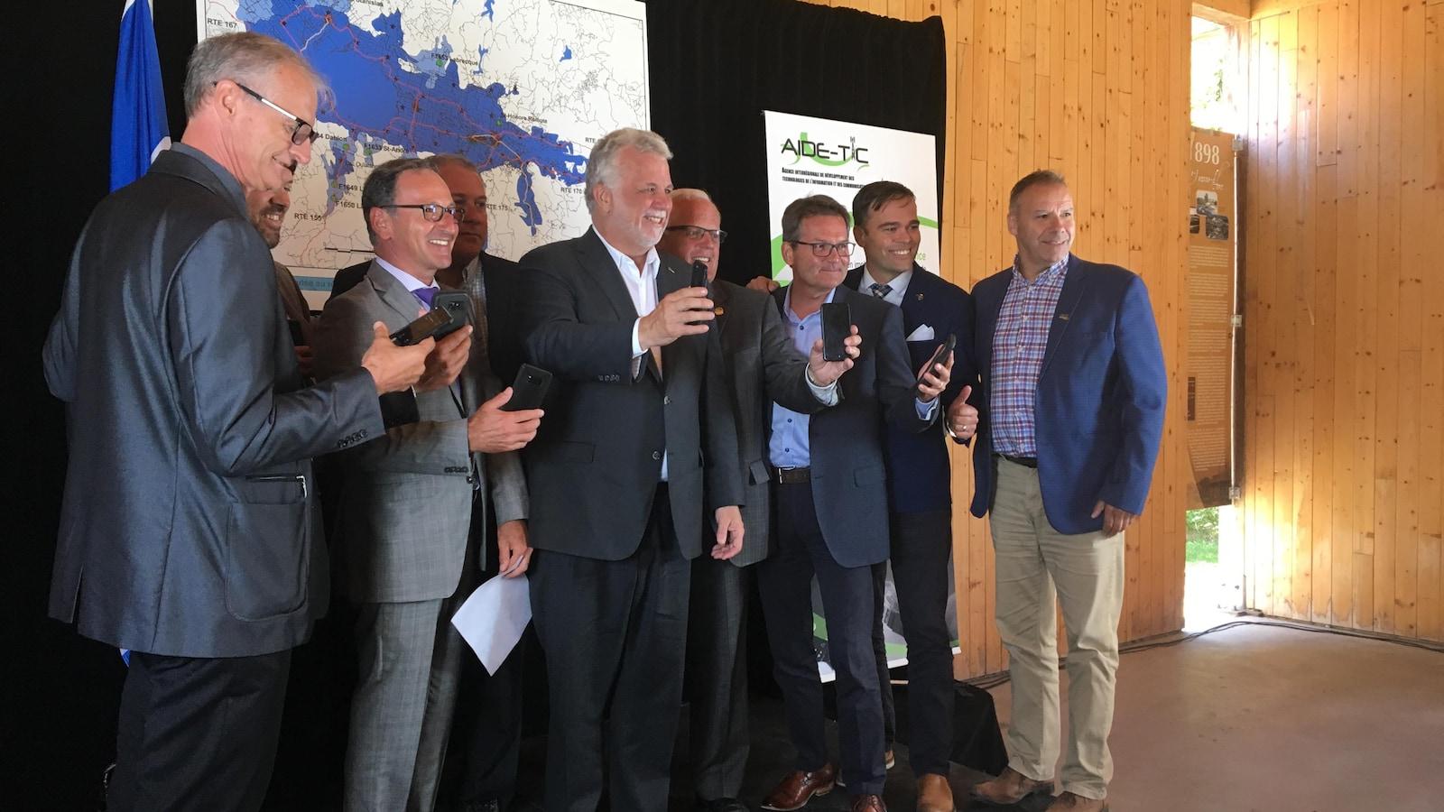 Les élus du Saguenay-Lac-Saint-Jean posent devant une carte de la région avec leur cellulaire en main.