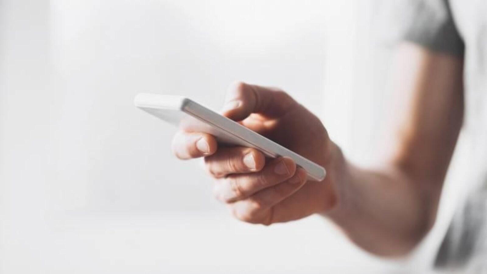 Une personne tient un cellulaire à la main.