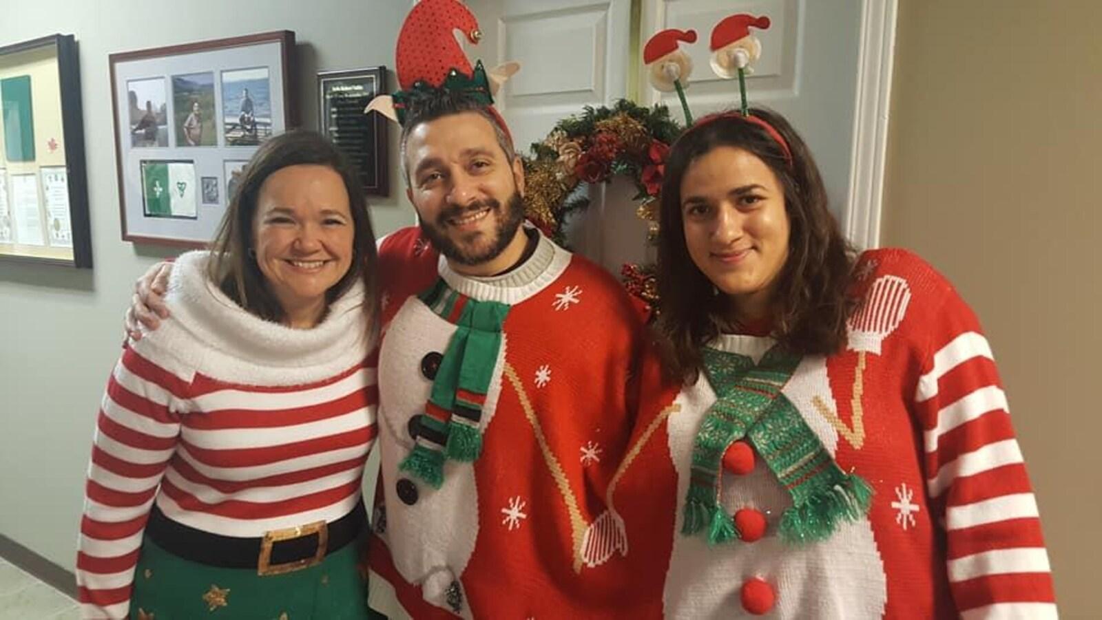 Trois personnes souriantes, habillées selon une thématique de Noël.