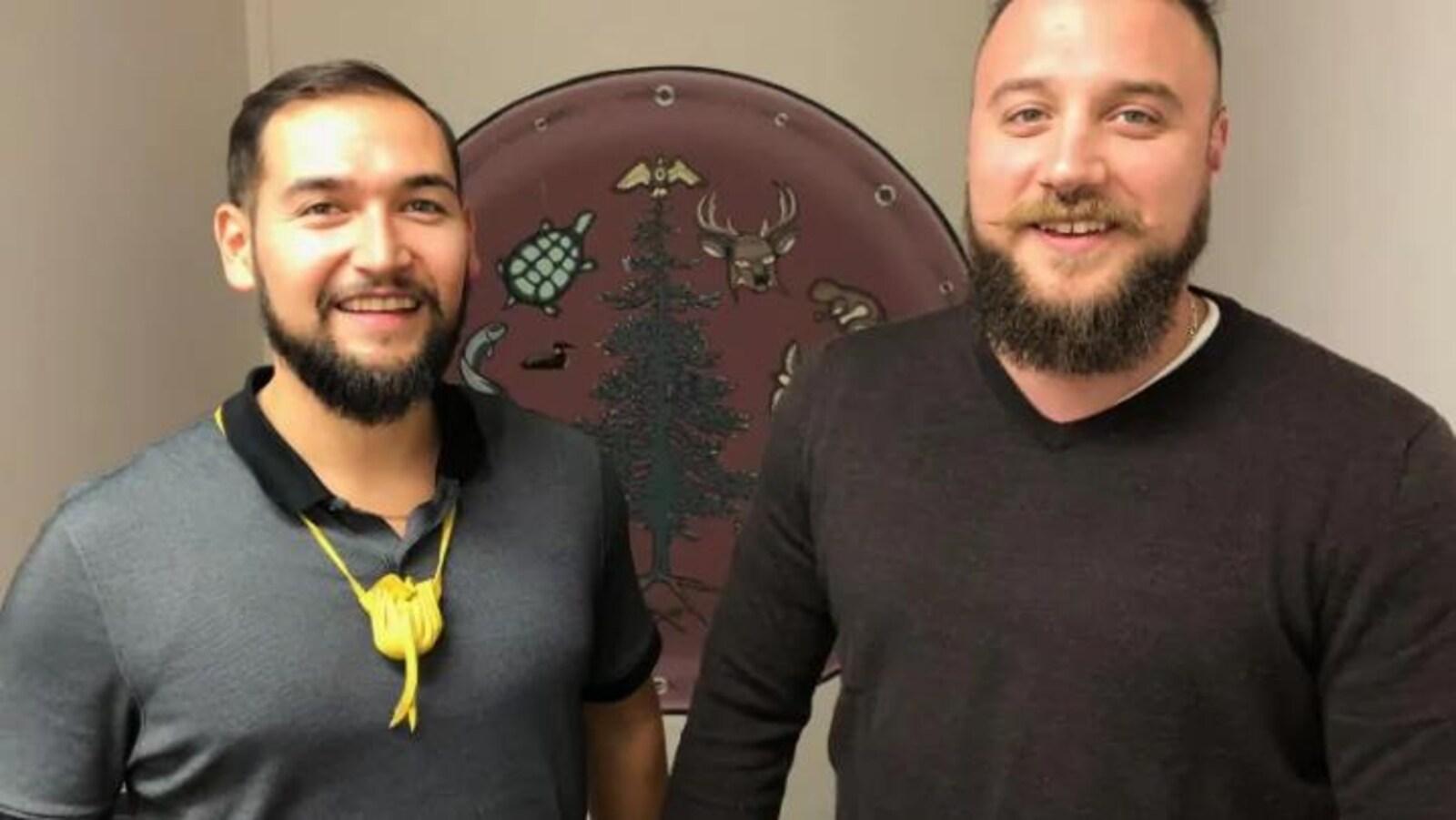 Jonathon Araujo et  Jacob Taylor  sourient, ils portent tous les deux une courte barbe, un chandail bleu pour Jonathon et un chandail bordeau pour Jacob