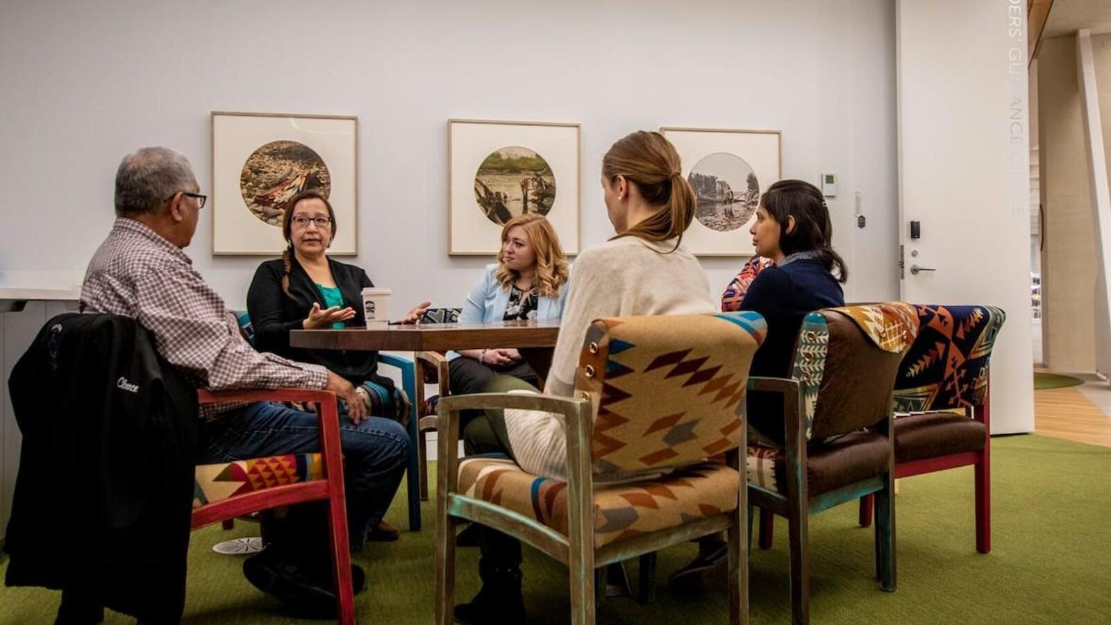Des autochtones assis autour d'une table en train de discuter