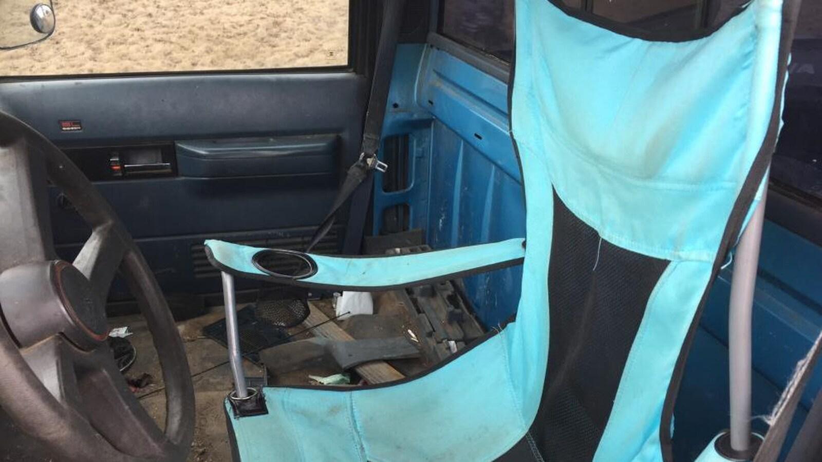 Une chaise pliante à l'avant d'une camionnette.