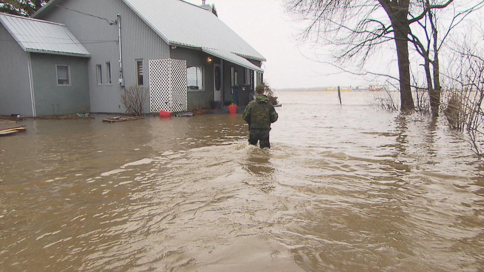 Militaire qui va vers une maison avec de l'eau jusqu'aux cuisses.