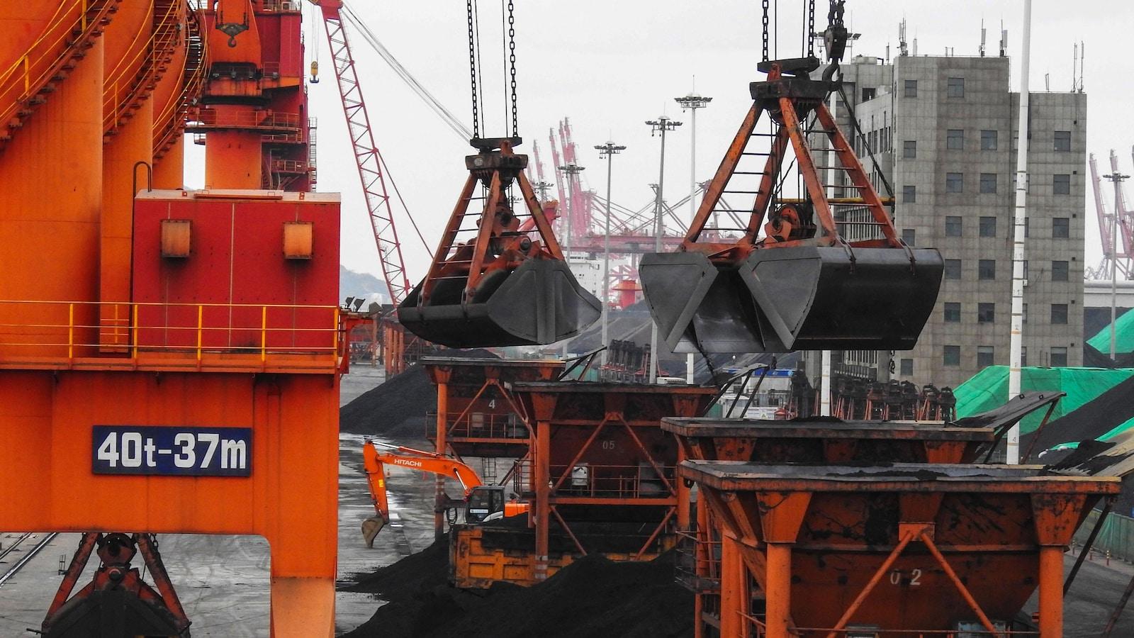 Des grues transfèrent des quantités de charbon dans des conteneurs dans un port chinois.