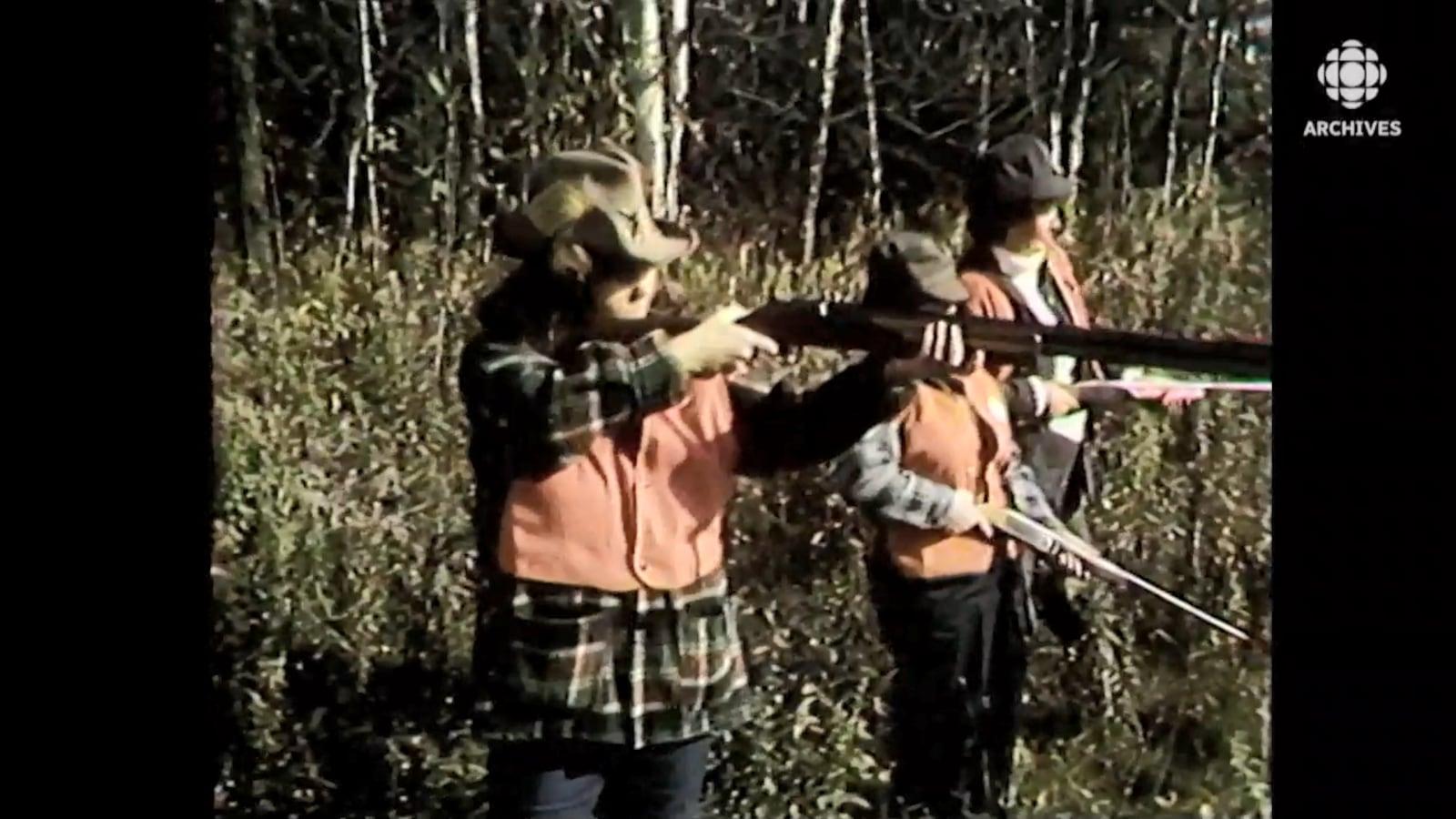 Trois femmes avec des dossards oranges tirent au long fusil dans un forêt.