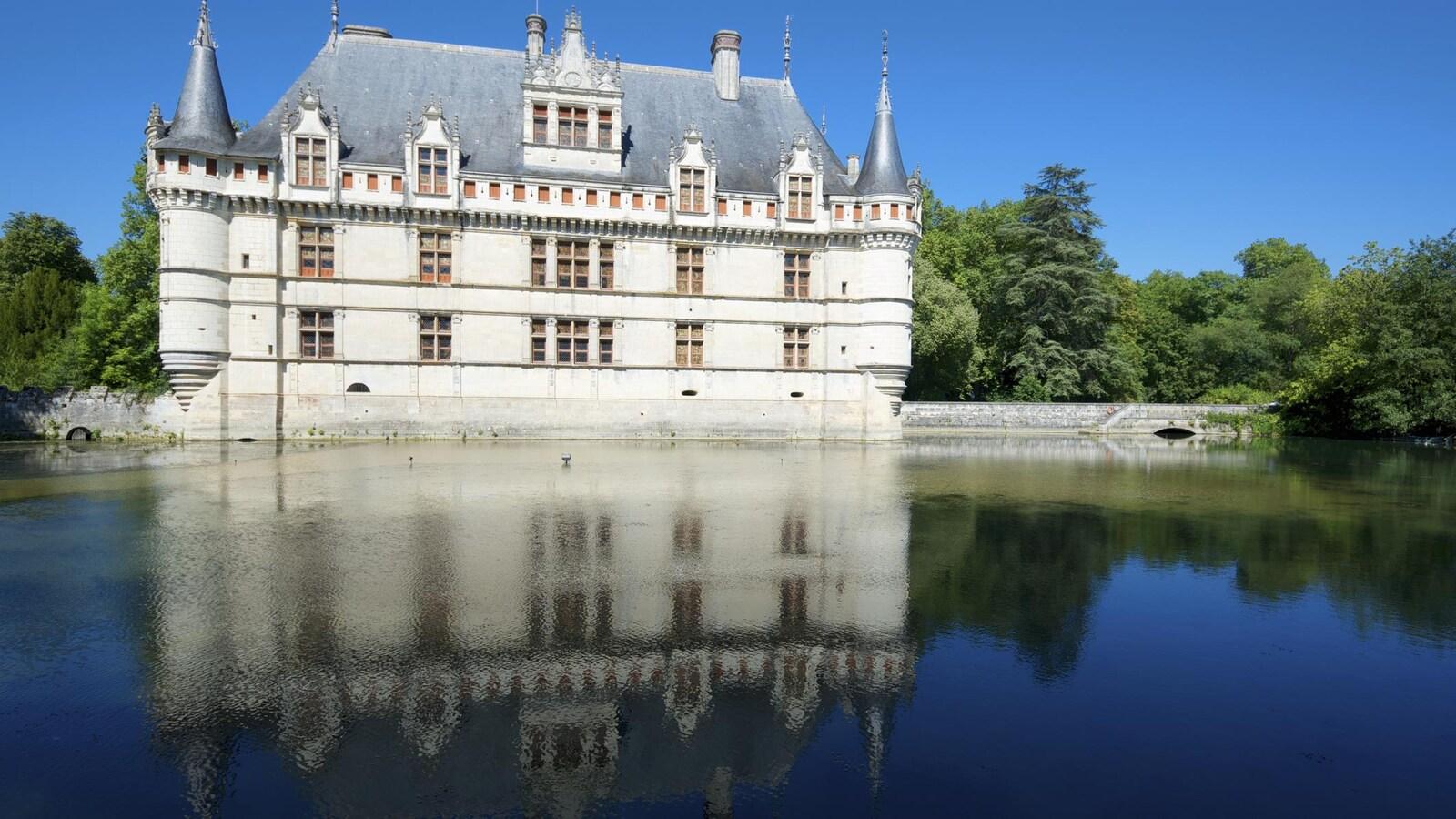 On voit le reflet du château dans l'eau.