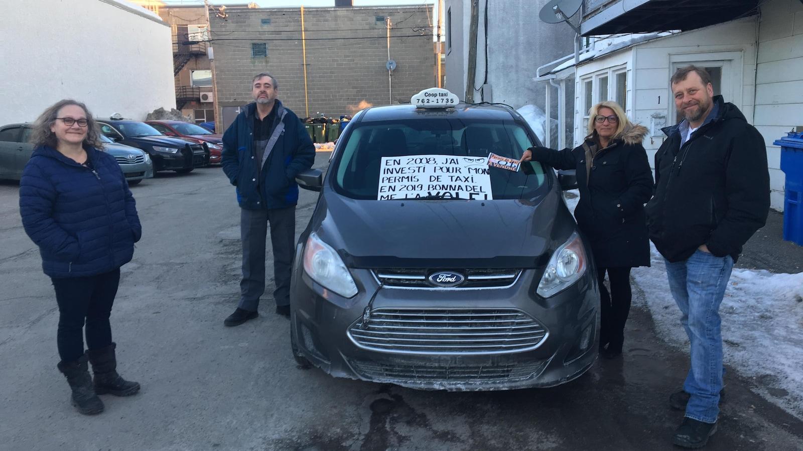 Quatre chauffeurs de taxi se tiennent près d'un taxi. Sur une pancarte il est inscrit « En 2008, j'ai investi pour mon permis de taxi. En 2019 Bonnadel me l'a volé. À vendre zéro dollar ».
