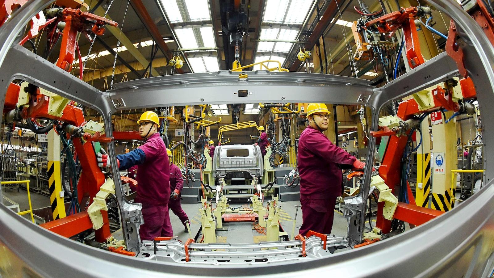 Des employés travaillent sur une chaîne de production fabriquant des camions légers dans une usine de JAC Motors à Weifang, province de Shandong, Chine, le 30 novembre 2018.
