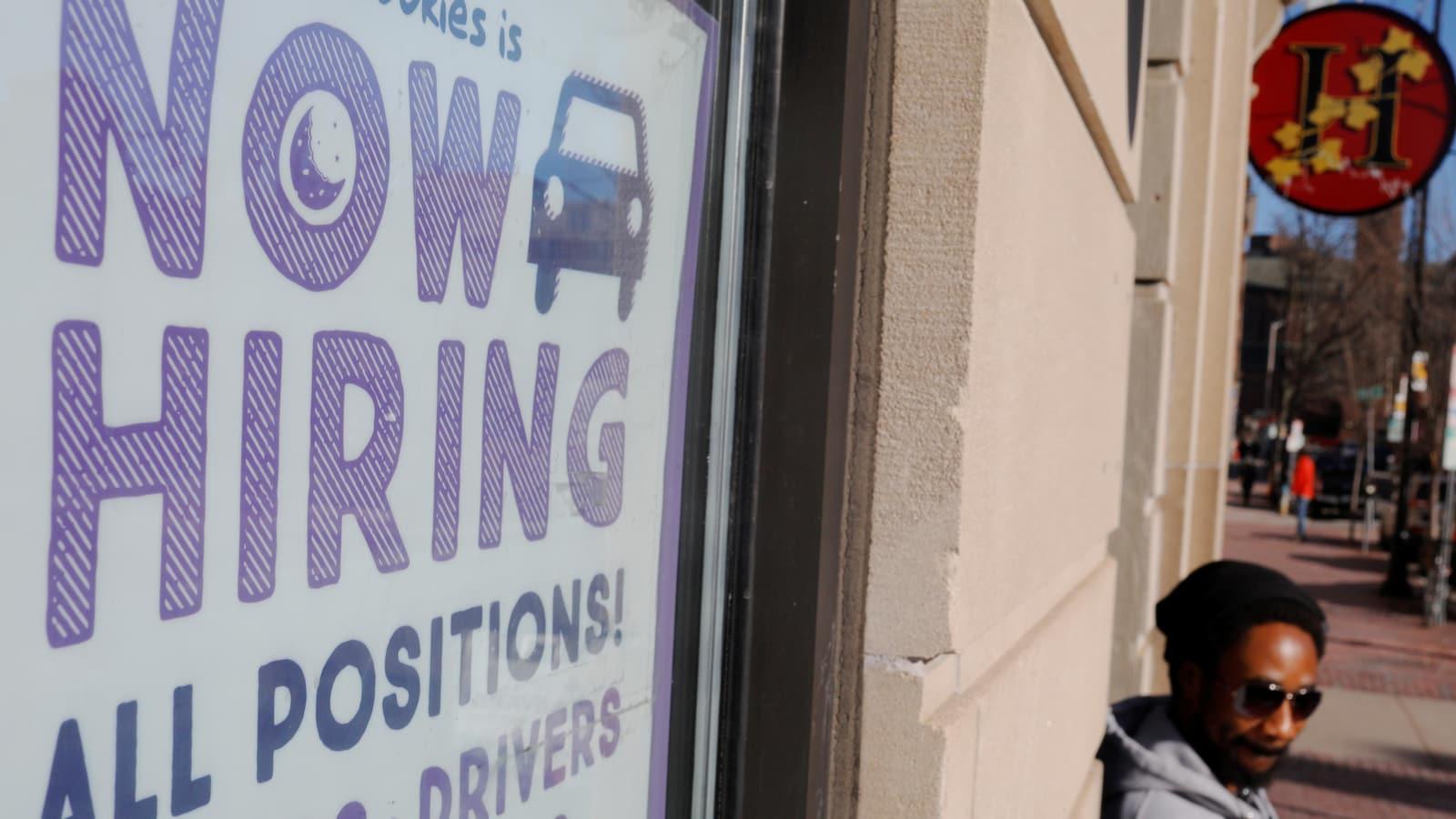 Un homme est appuyé sur un mur près d'une pancarte invitant les demandeurs d'emploi à soumettre leur candidature