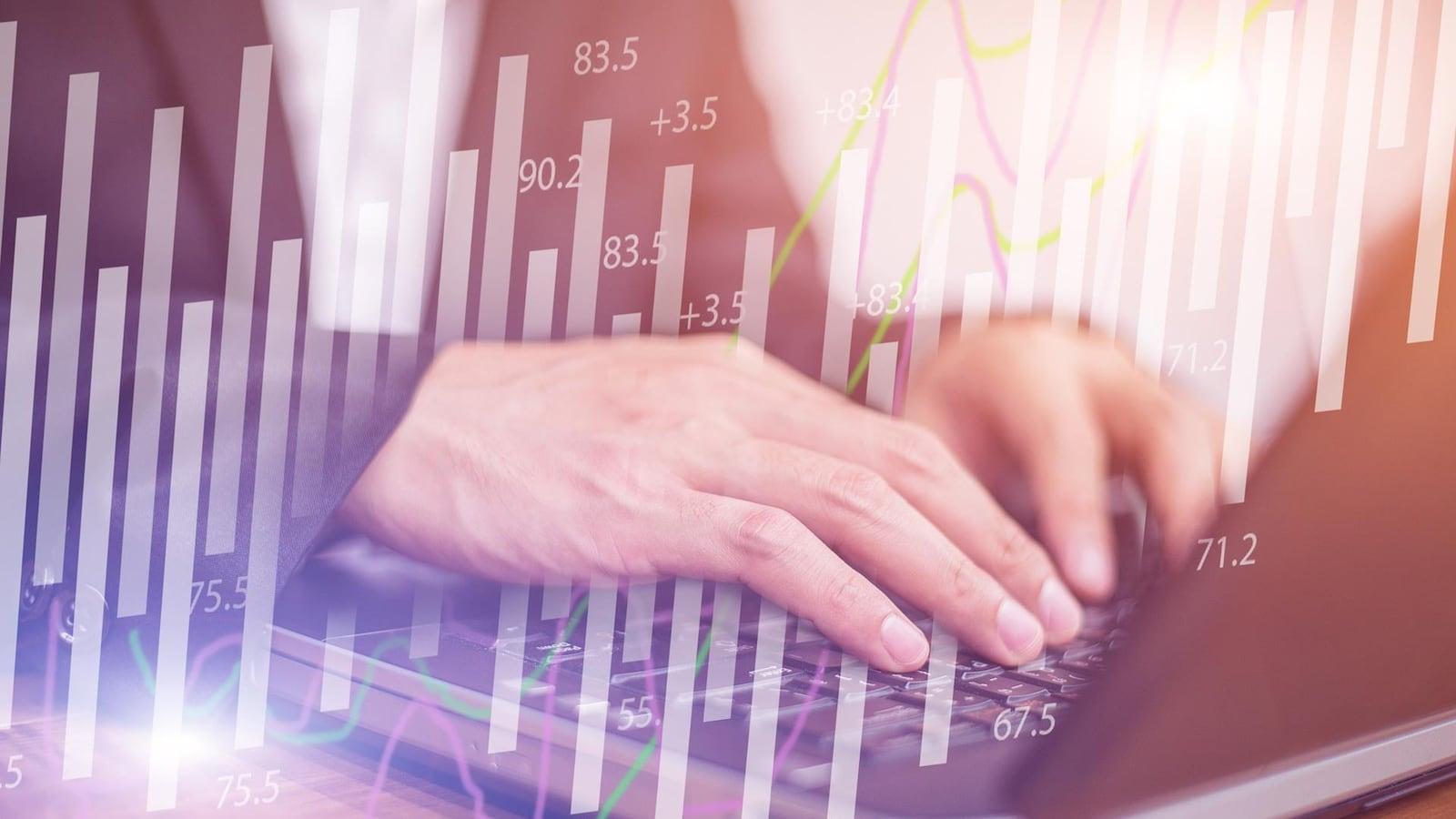 Photo de mains qui tapent sur un clavier d'ordinateur, des courbes et des chiffres en arrière-plan.