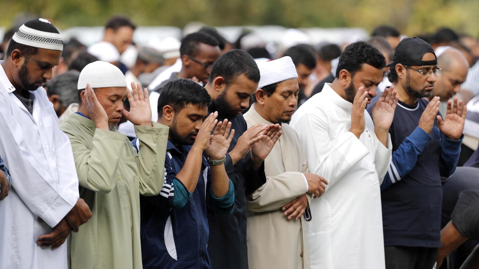 Des personnes debout prient les yeux fermés et les mains ouvertes.