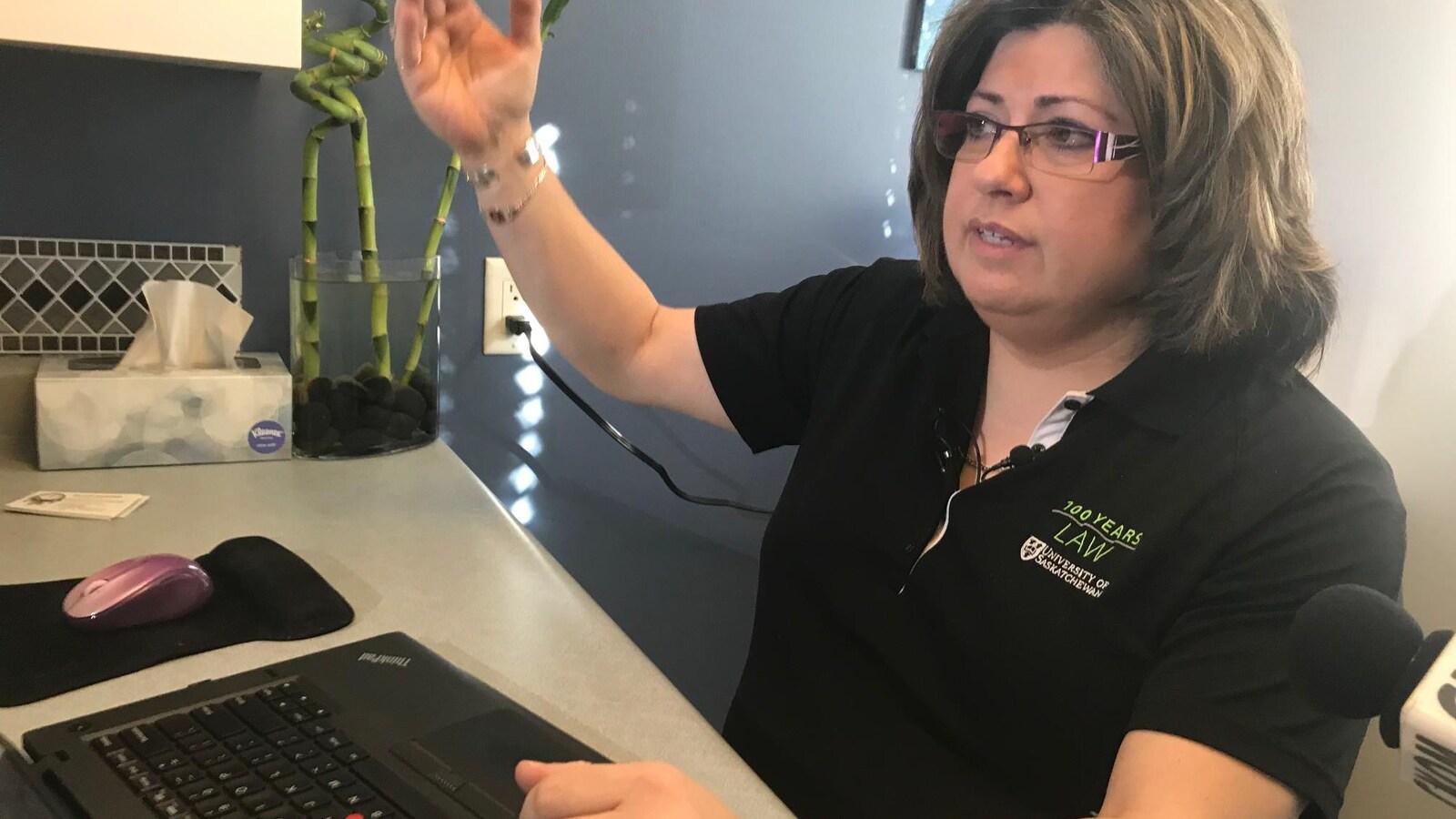 L'avocate devant son ordinateur, qui s'exprime avec de grands mouvements de bras.
