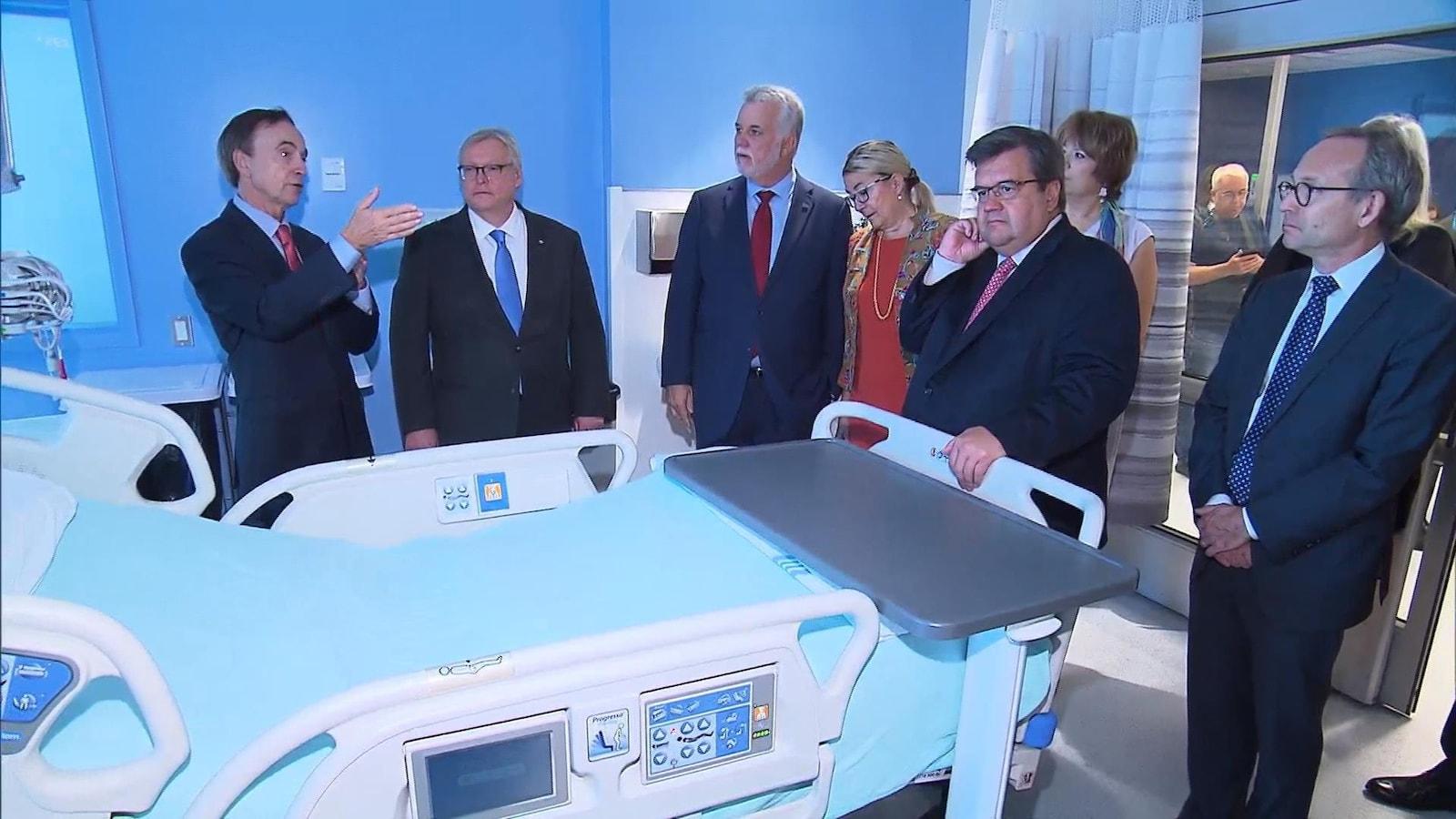 Le PDG du CHUM, Fabrice Brunet, le ministre Gaétan Barrette, le premier ministre Philippe Couillard, la ministre Hélène David, le maire de Montréal, Denis Coderre, et le ministre Martin Coiteux lors de la visite d'une chambre.