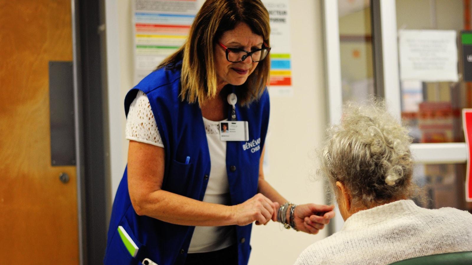 Ghyslaine Desnoyers est bénévole à l'urgence depuis huit ans. Elle répond aux questions des patients, les dirige et les rassure.