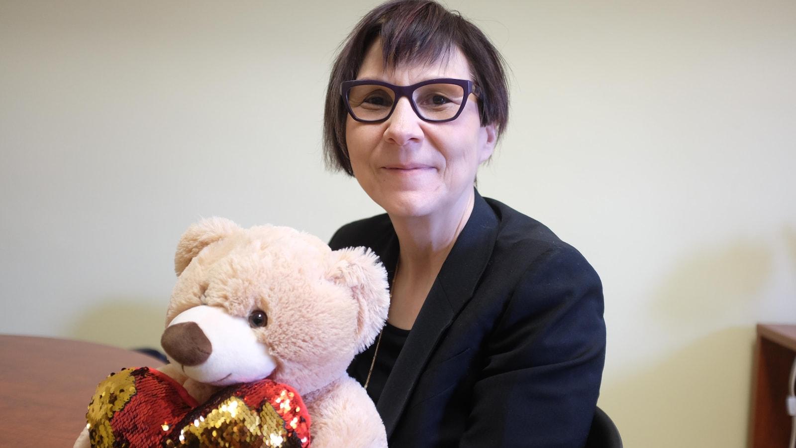 La professeure Cindy Blackstock pose avec un ourson, mascotte de sa cause, dans son bureau à l'Université McGill.