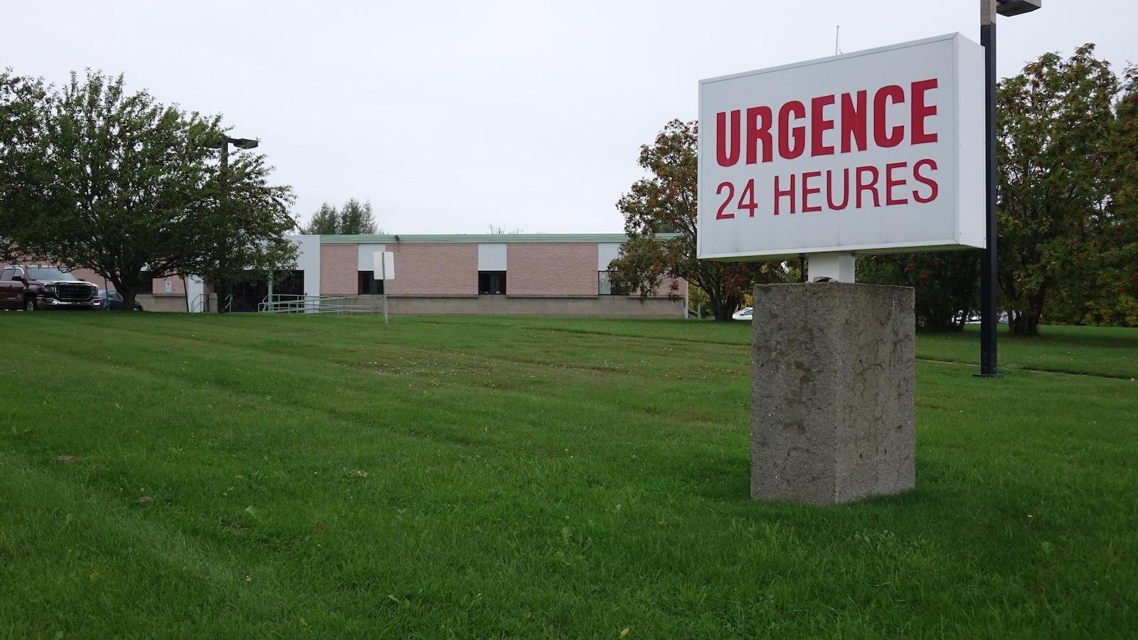 Affiche Ugence 24 heures et bâtiment derrière