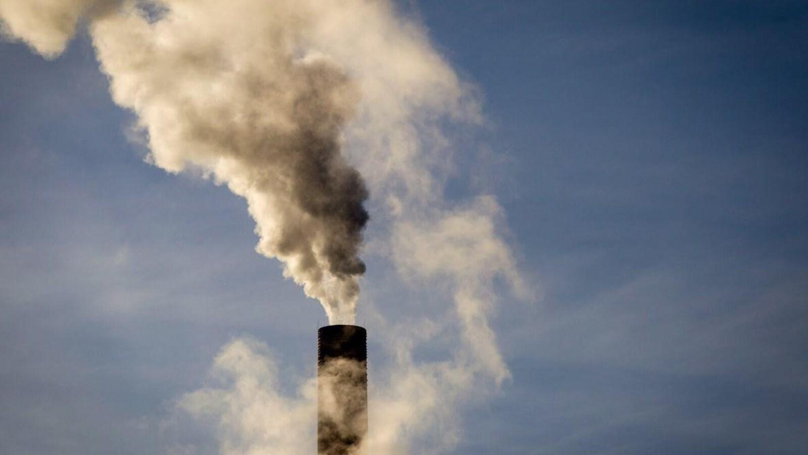 Une cheminée crache de l'épaisse fumée.