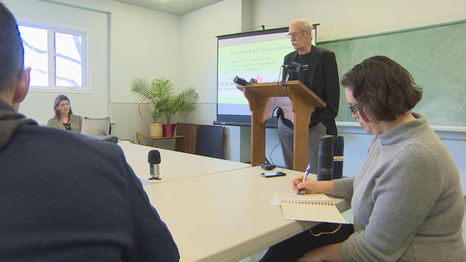 Un homme devant un lutrin parle à des gens qui prennent des notes.