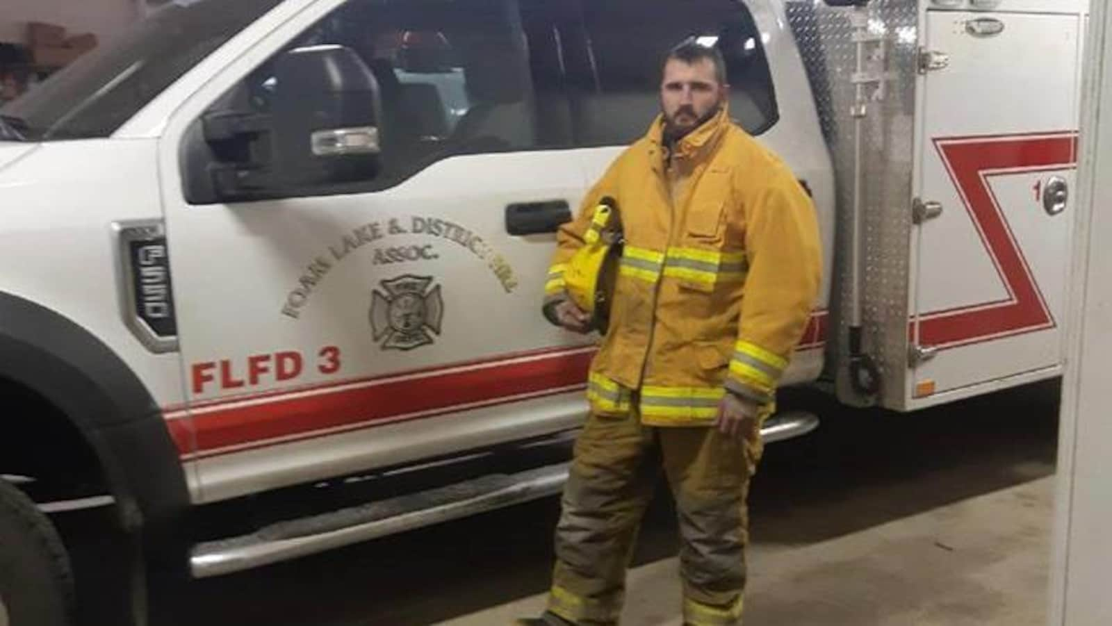 Le pompier bénévole Cole Maksymytz tient son casque sous le bras devant une ambulance.