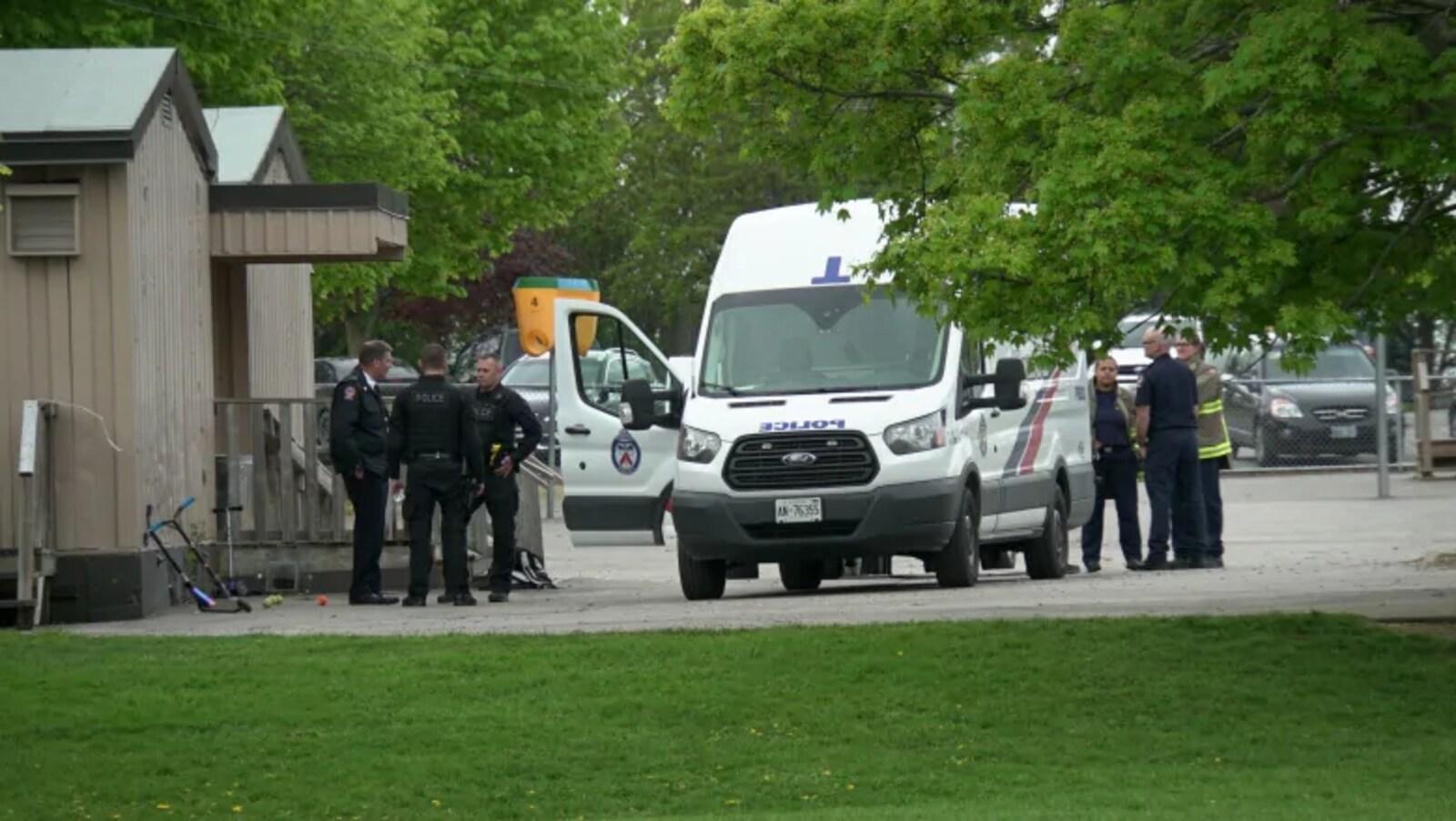 Photo de policiers et de pompiers qui se tiennent debout à côté d'une camionnette de police.