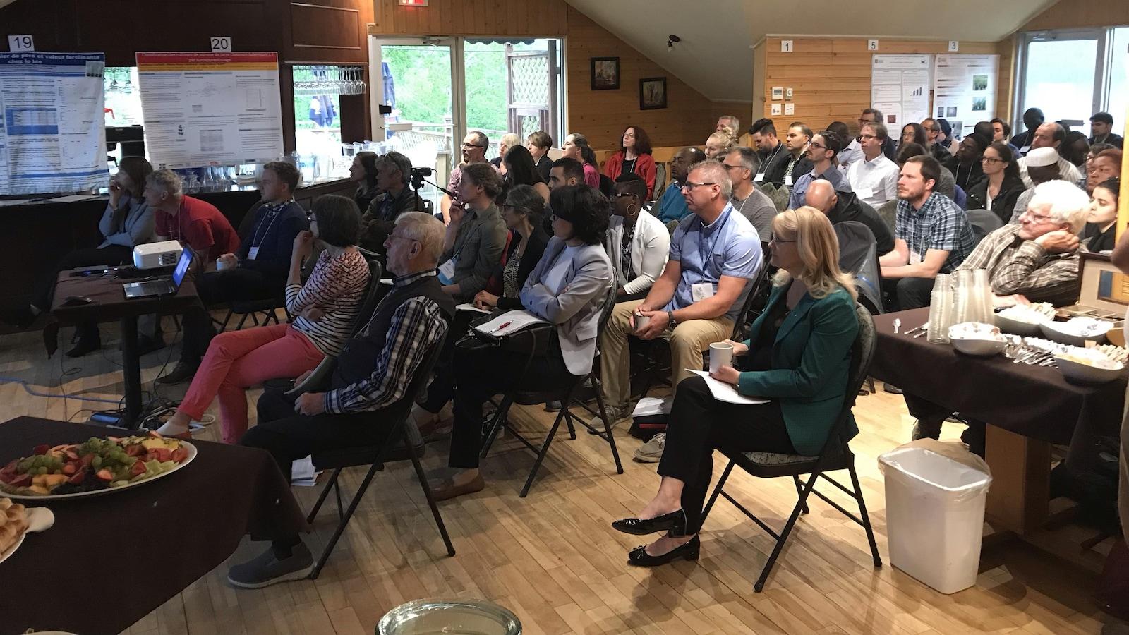 Quelques dizaines de gens écoutent une présentation lors d'un colloque.