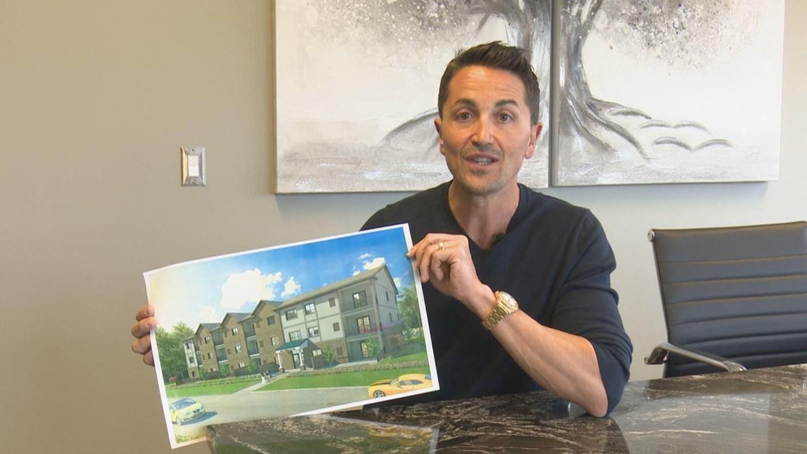 Un homme assis derrière une table présente le plan d'un édifice.