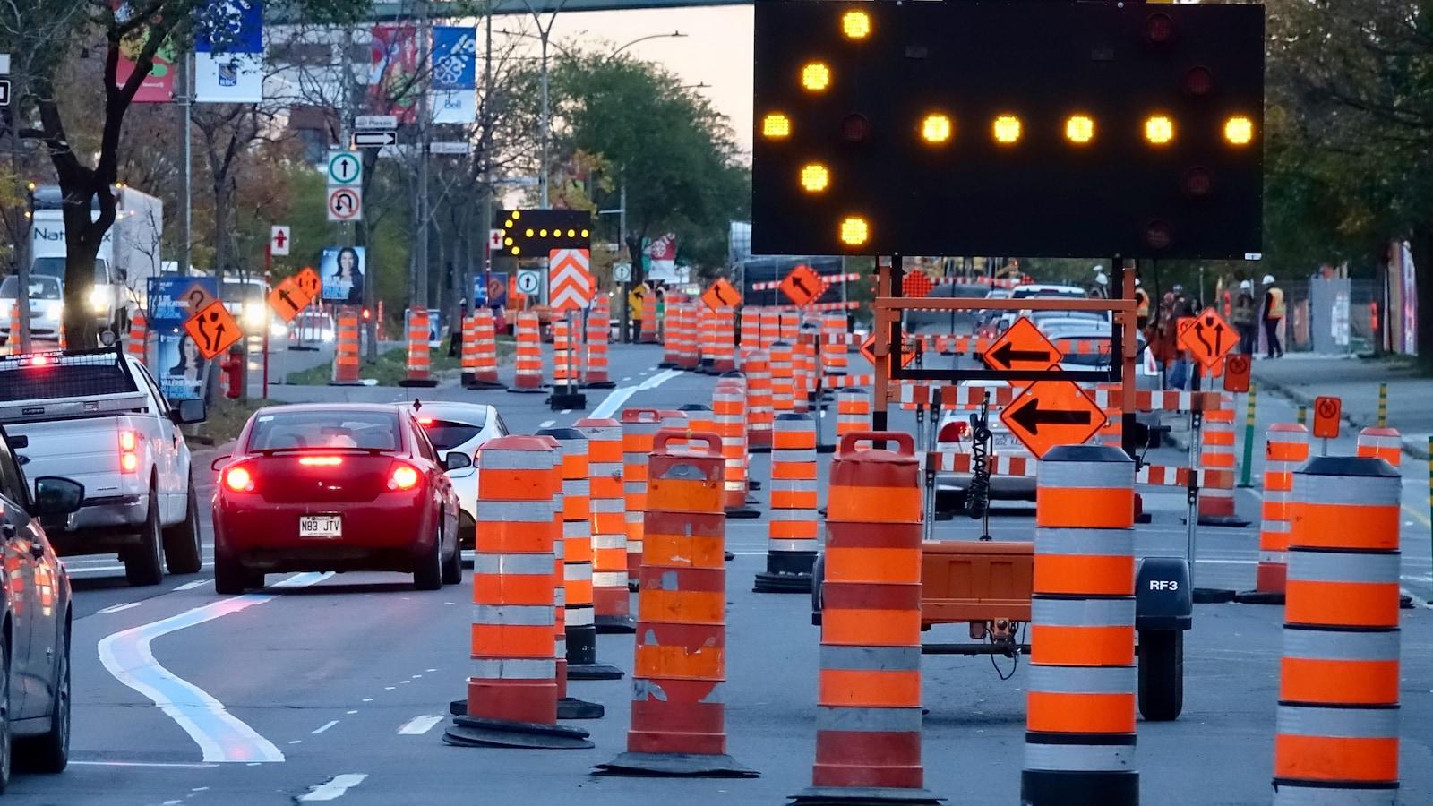 Des cônes de sécurité et des voitures sur un boulevard urbain