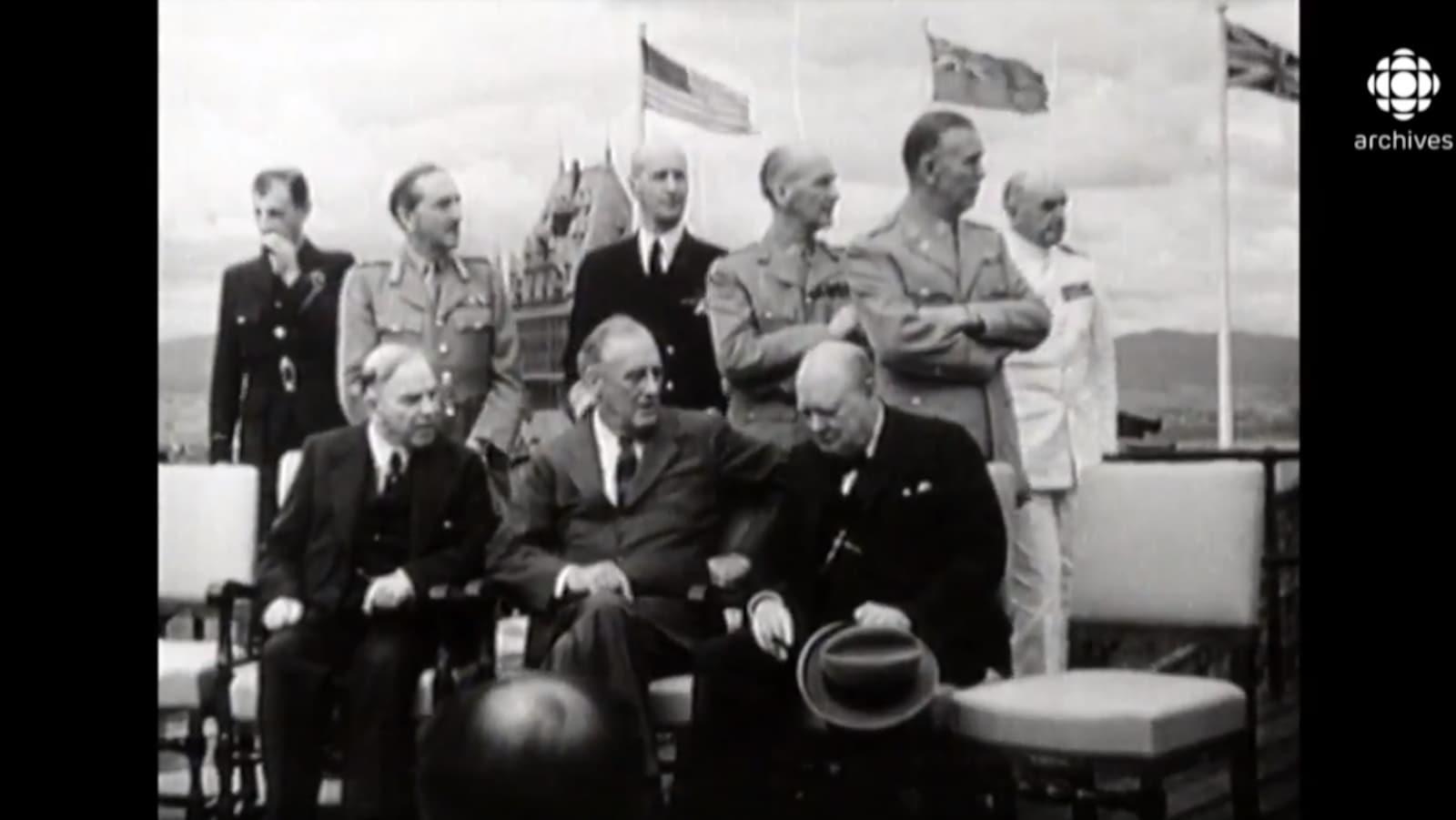 Le premier ministre canadien Mackenzie King, le premier ministre britannique Winston Churchill et le président américain Franklin D. Roosevelt sont assis devant le Château Frontenac avec des généraux debout derrière eux.