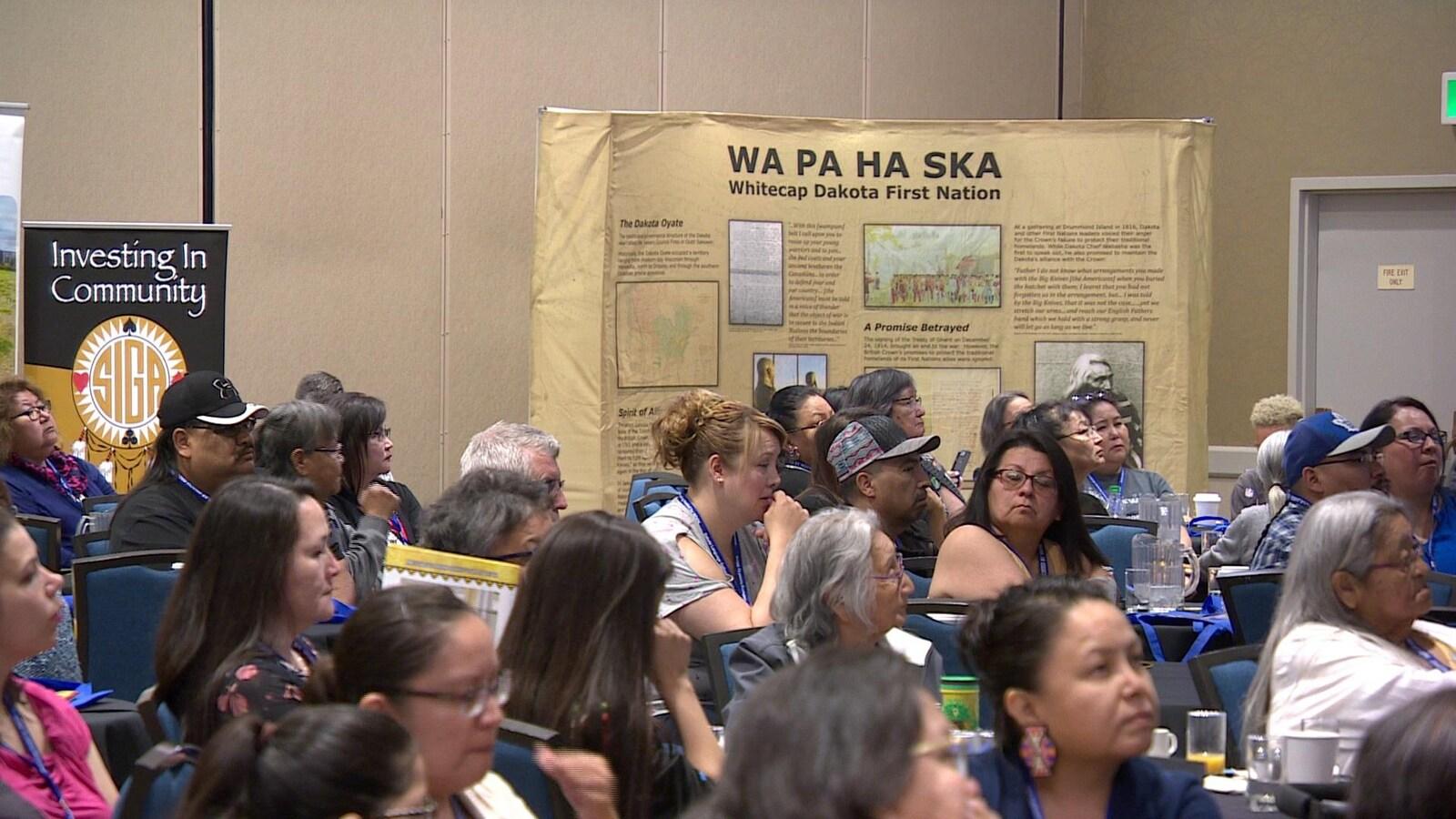 Plusieurs visiteurs assis à la conférence sur l'avenir de la langue Dakota.