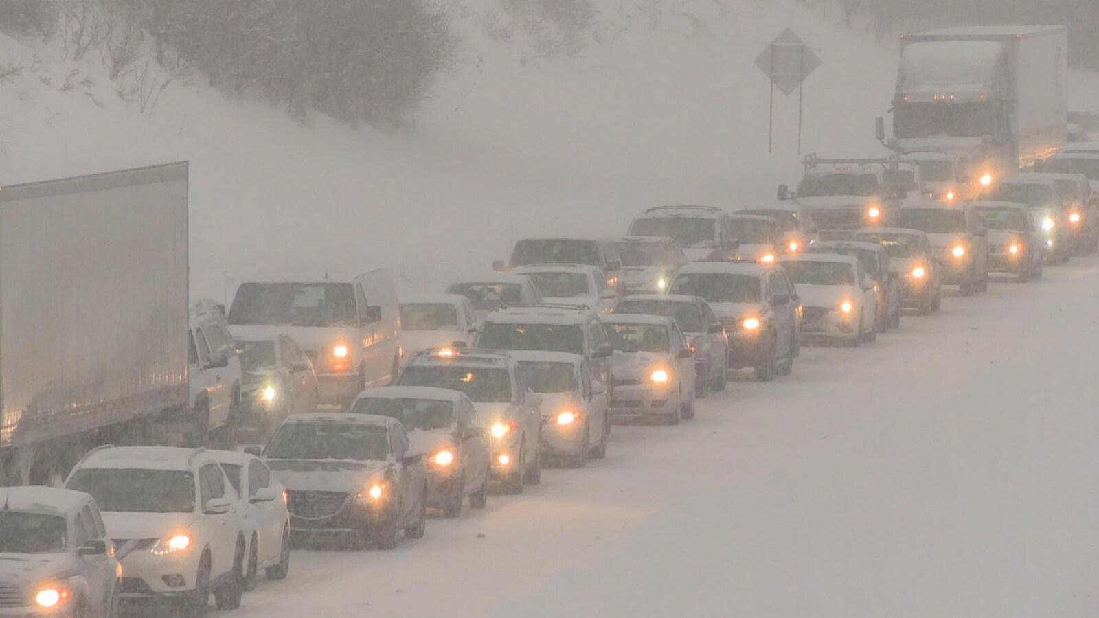 Deux rangées de voitures dans la neige sur une autoroute congestionnée.