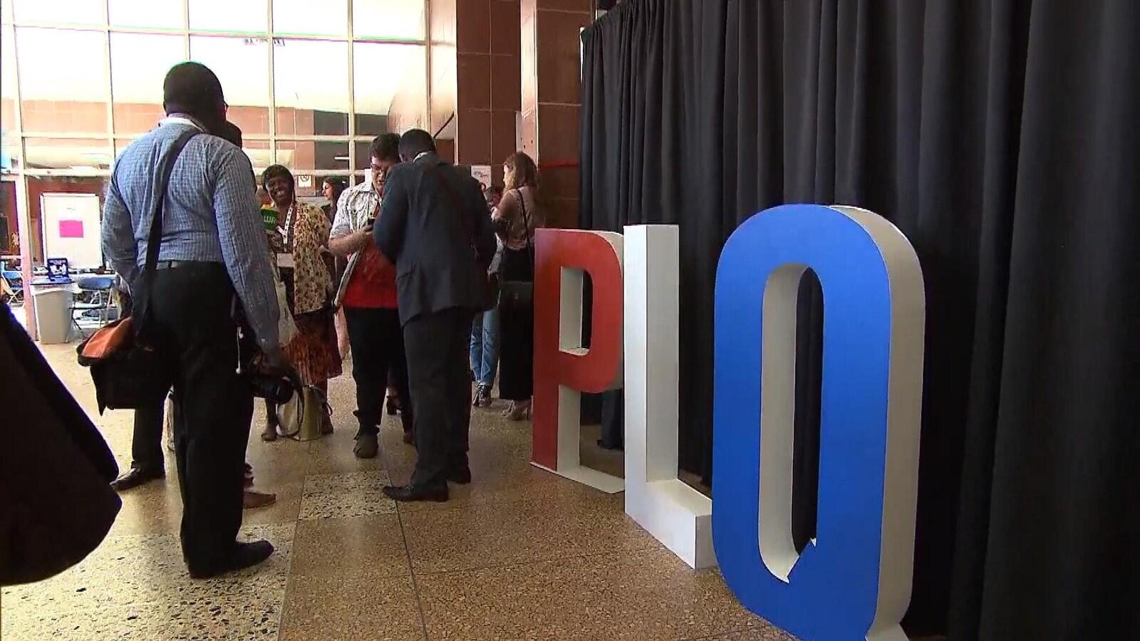 Plusieurs personnes entrain de discuter dans une salle à côté d'une installation à l'effigie du PLQ