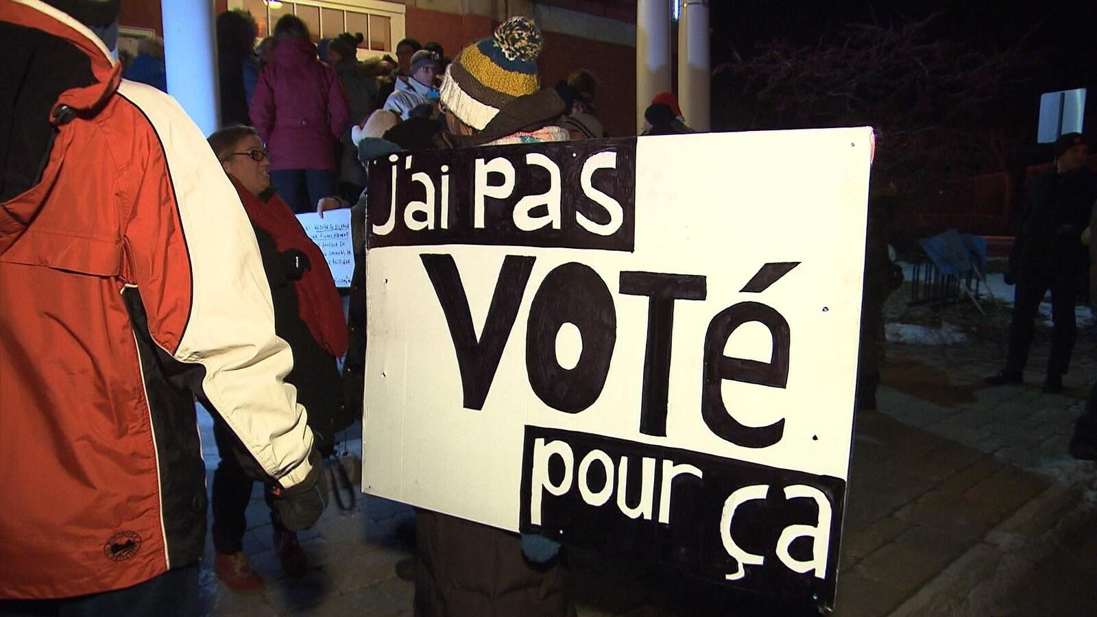Des dizaines de personnes sont réunies à l'entrée de l'hôtel de ville de Chambly. L'une d'entre elles tient une pancarte où l'on peut lire : « J'ai pas voté pour ça. »