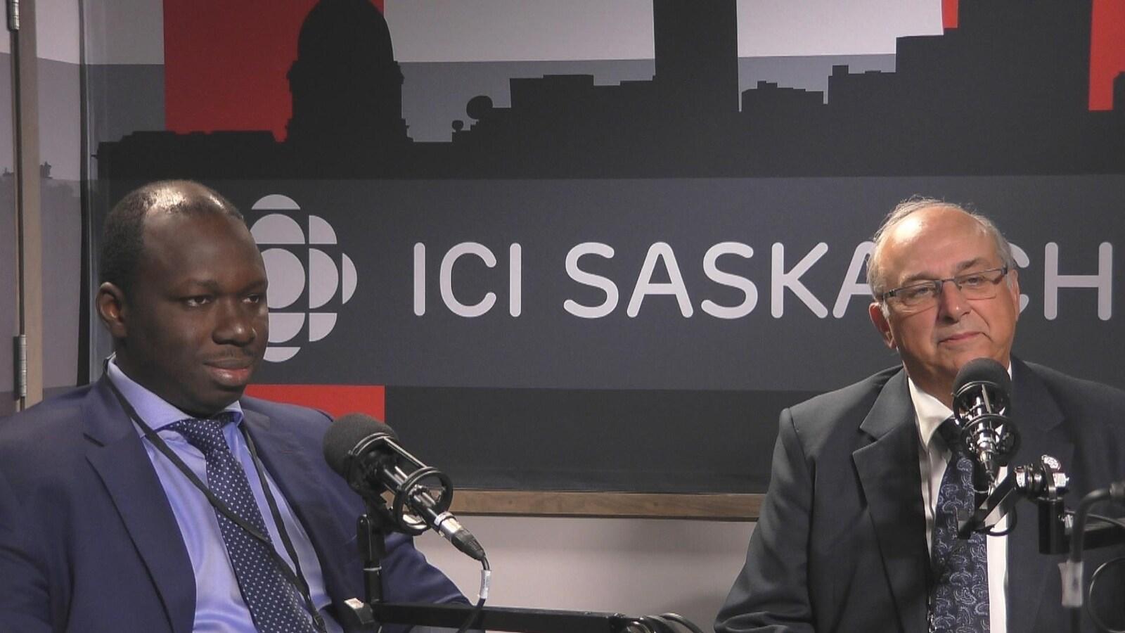 Deux hommes, en costume cravate, assis derrière des micros avec en arrière-plan une affiche d'ICI Saskatchewan.