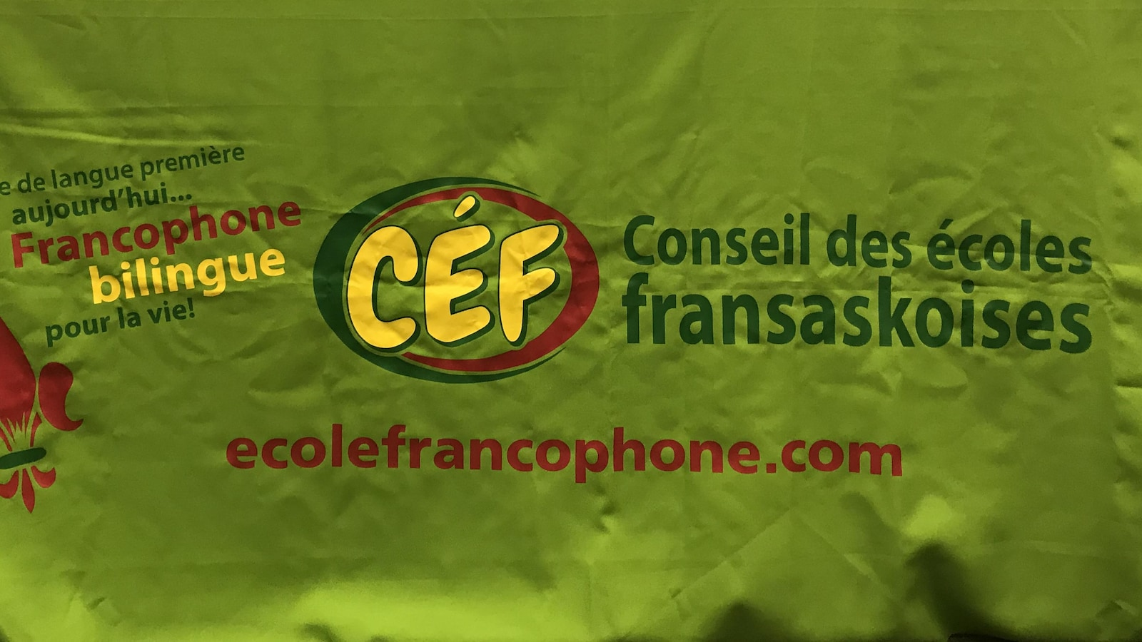 Une table aux couleurs du Conseil des écoles fransaskoises, avec le logo jaune et vert et rouge, ainsi que des éléments sur la table, comme une balance et un projecteur