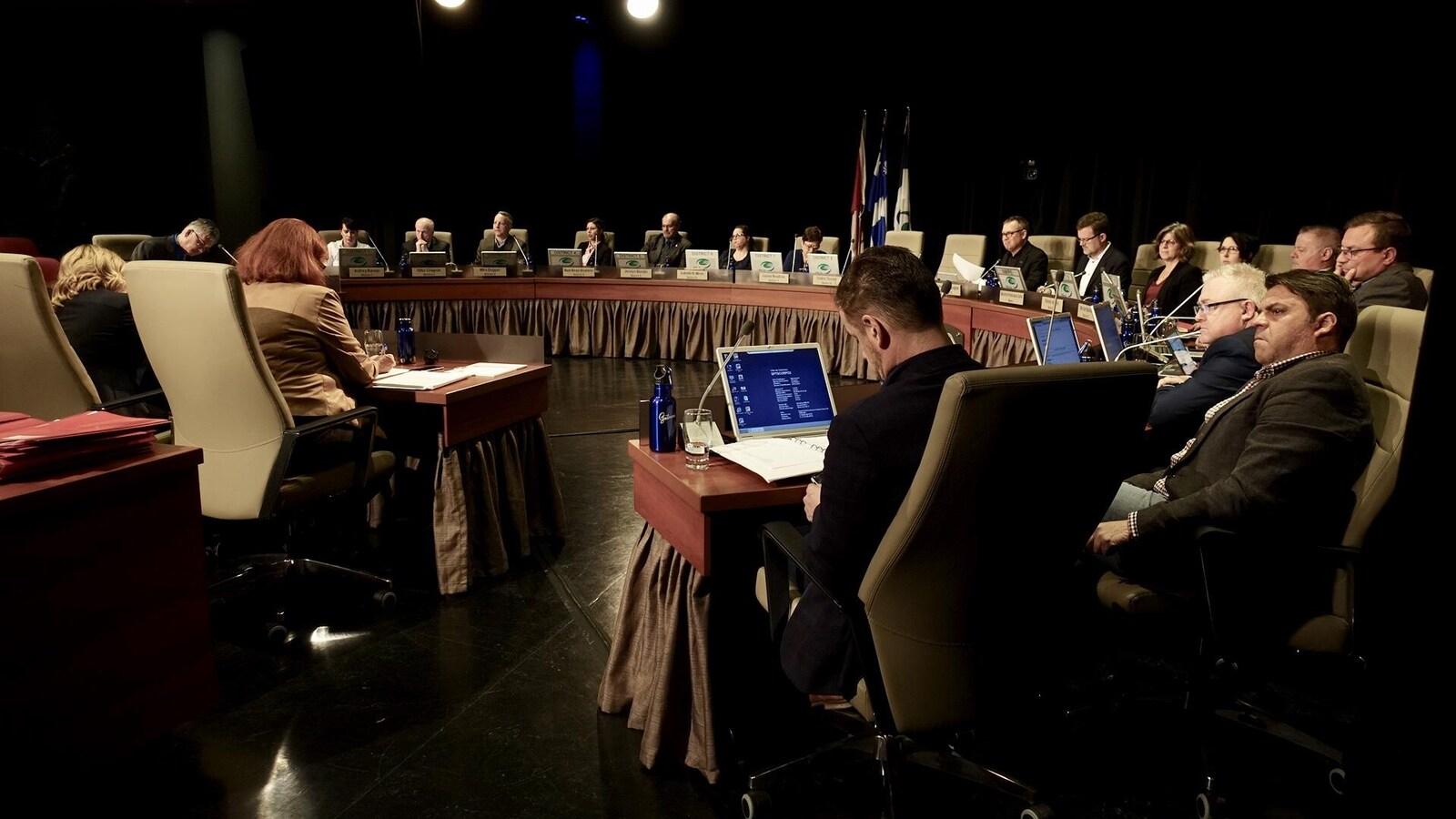 Des politiciens assis autour d'une grande table en forme de demi-cercle.