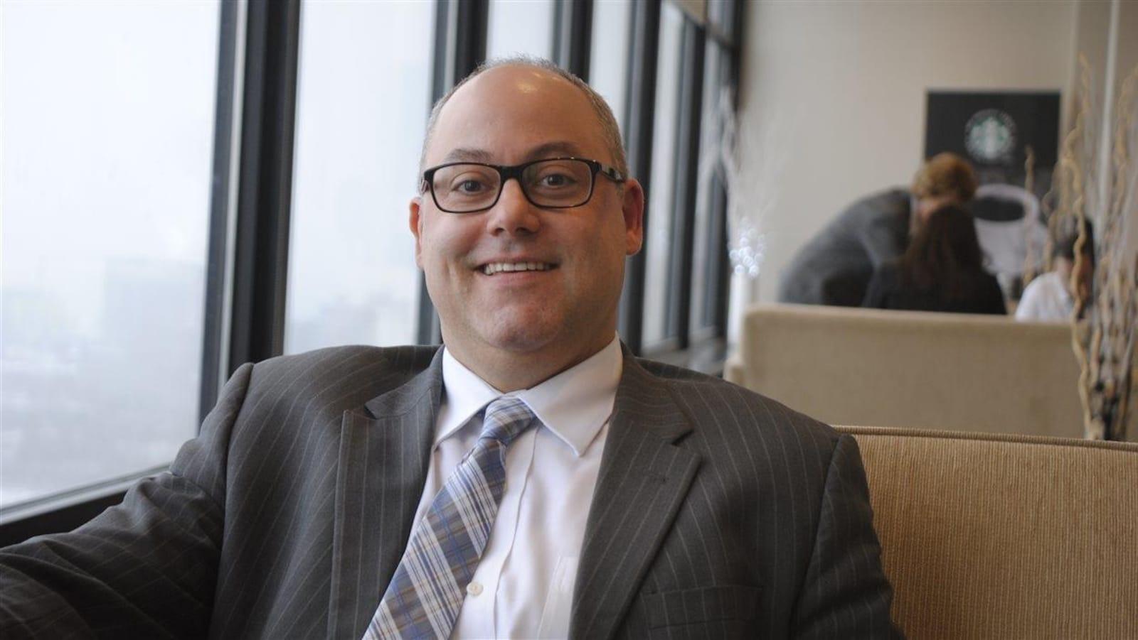 Marc Dumont, vêtu d'un veston et d'une cravate, sourit à la caméra.