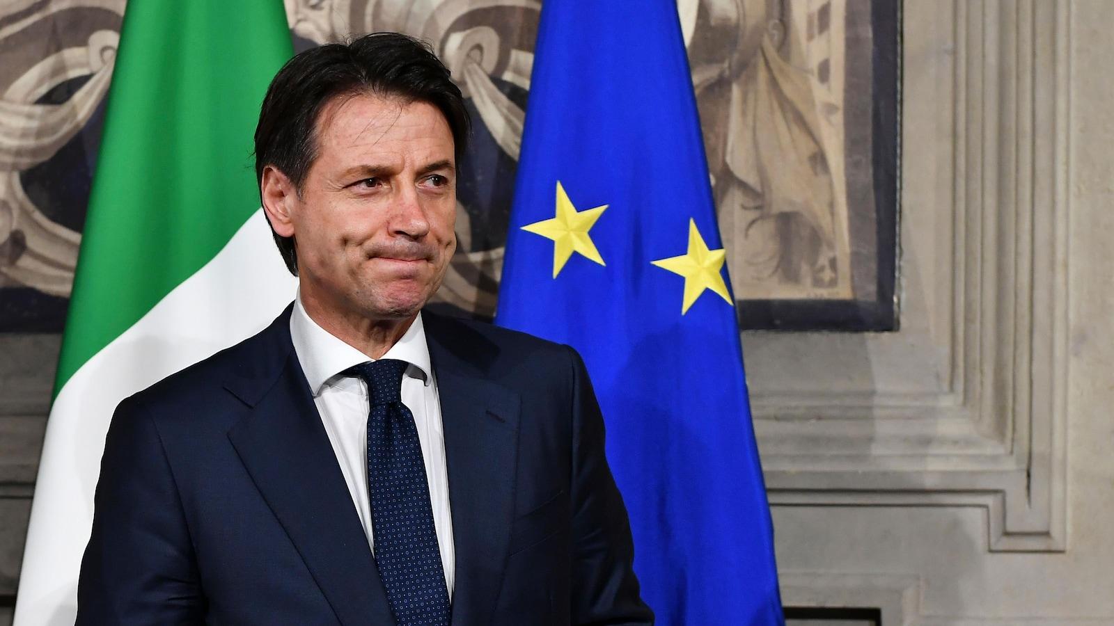 Giuseppe Conte, la mine basse, devant des drapeaux de l'Italie et de l'Union européenne.