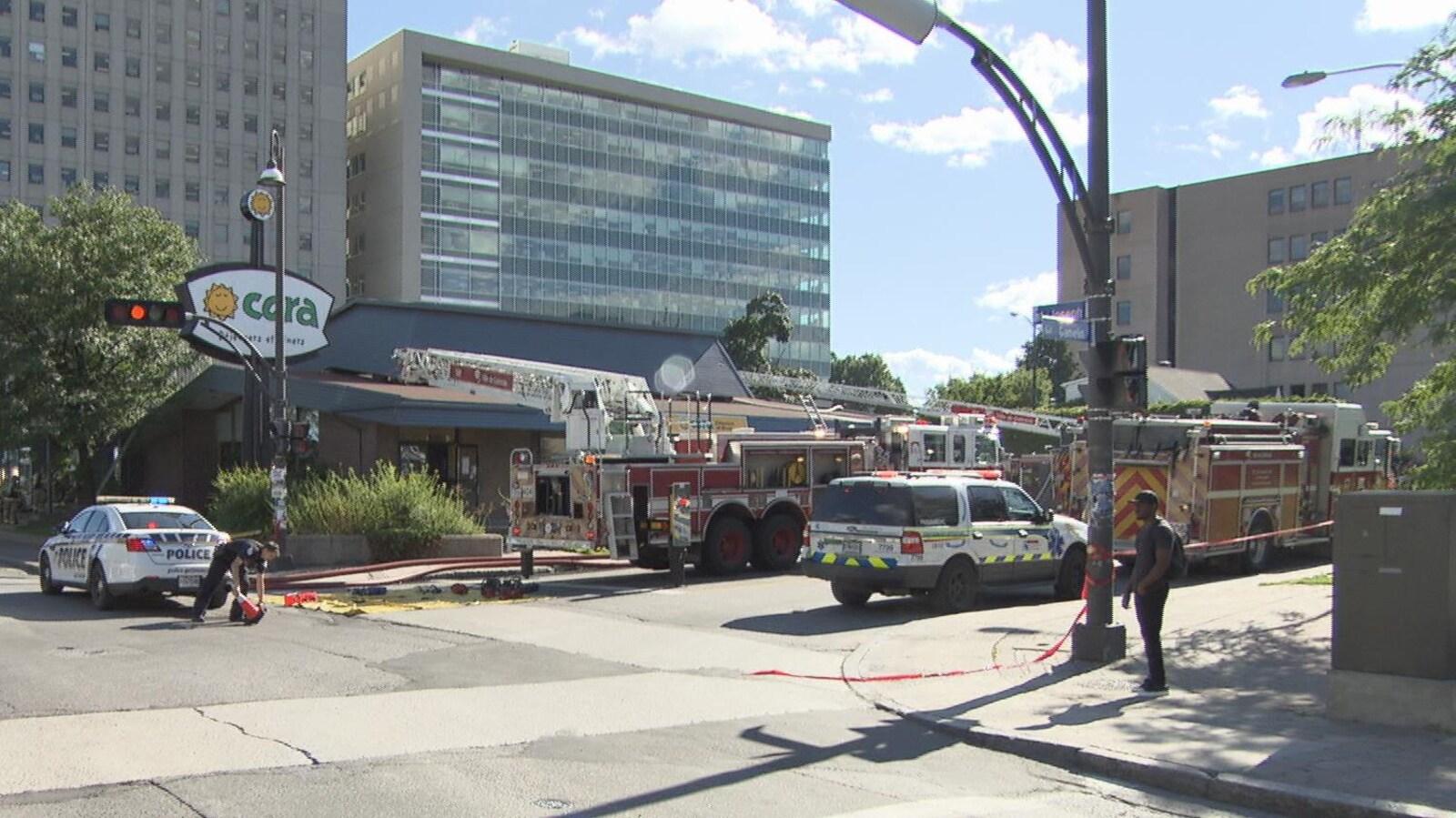 Des véhicules de police et des services incendie devant un restaurant qui a été la proie des flammes.