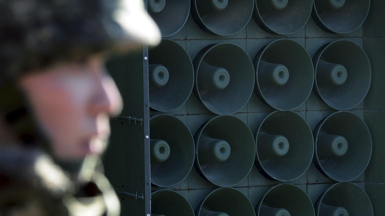 Gros plan sur un mur de haut-parleur. À l'avant-plan, un soldat sud-coréen de profil.