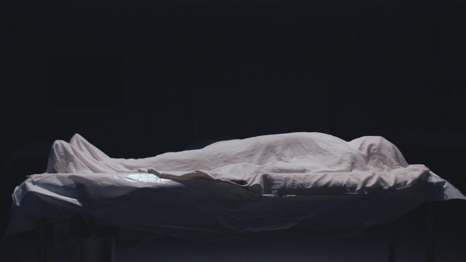 Un drap blanc recouvre un cadavre placé sur une table. Une lumière blanche l'éclaire de haut.