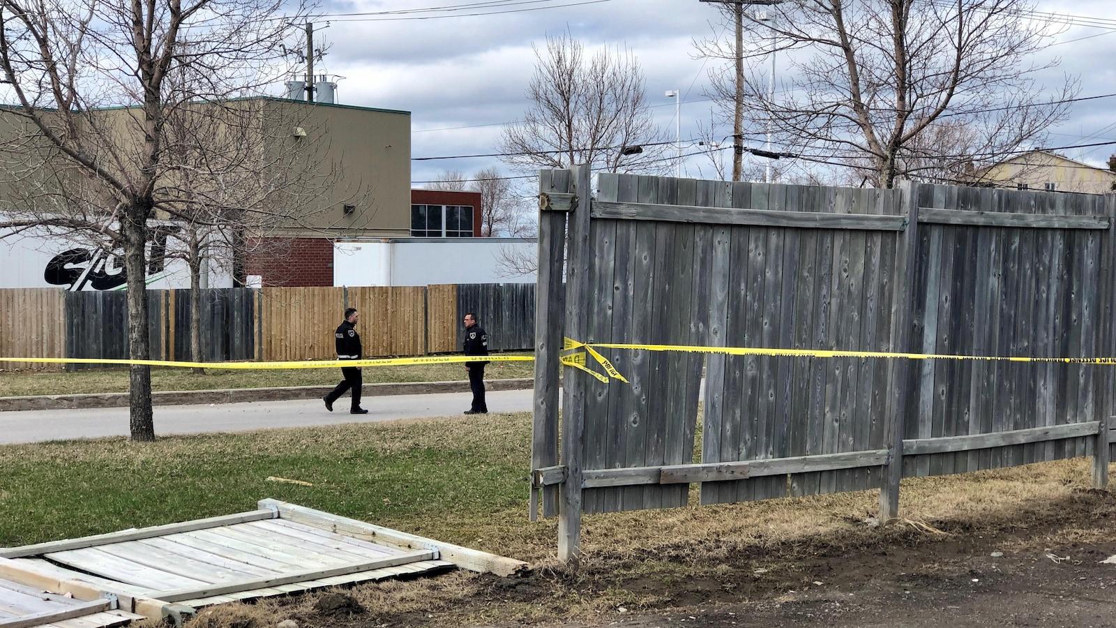 Des policiers derrière une banderole jaune délimitant un périmètre.