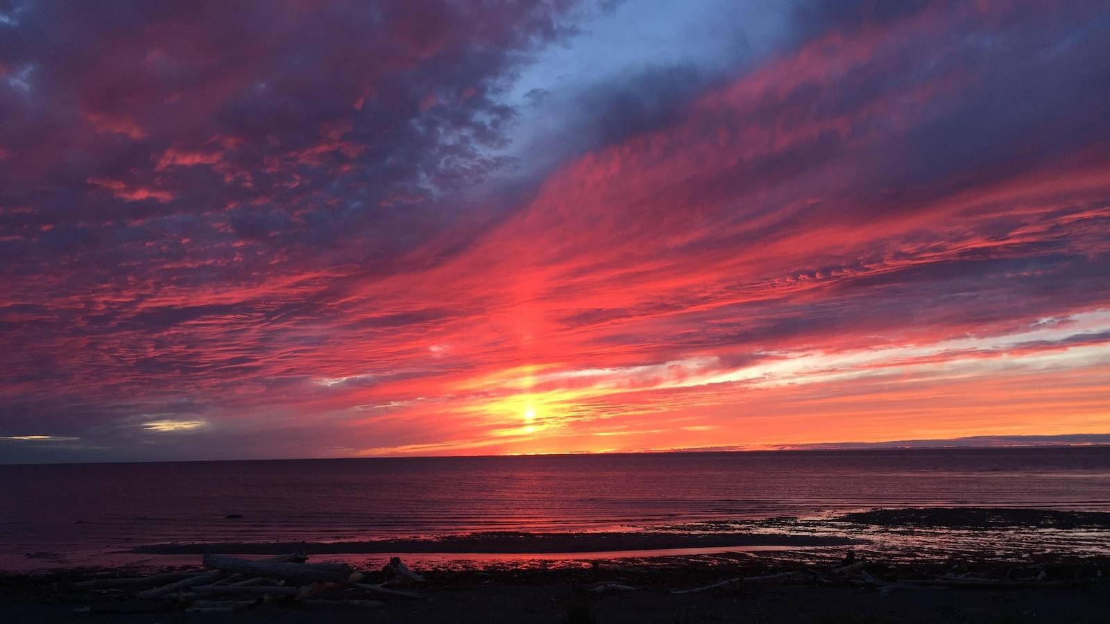 Le ciel est rose, violet, rouge et jaune au coucher de soleil.