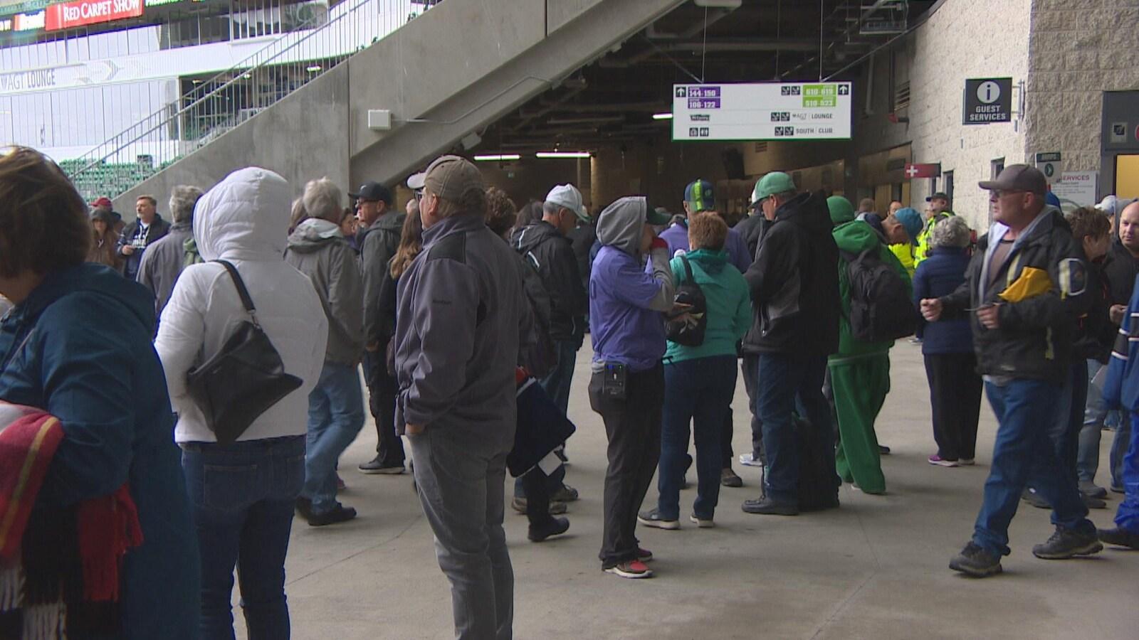 Des centaines d'amateurs de hockey junior marchent dans le stade Mosaic.