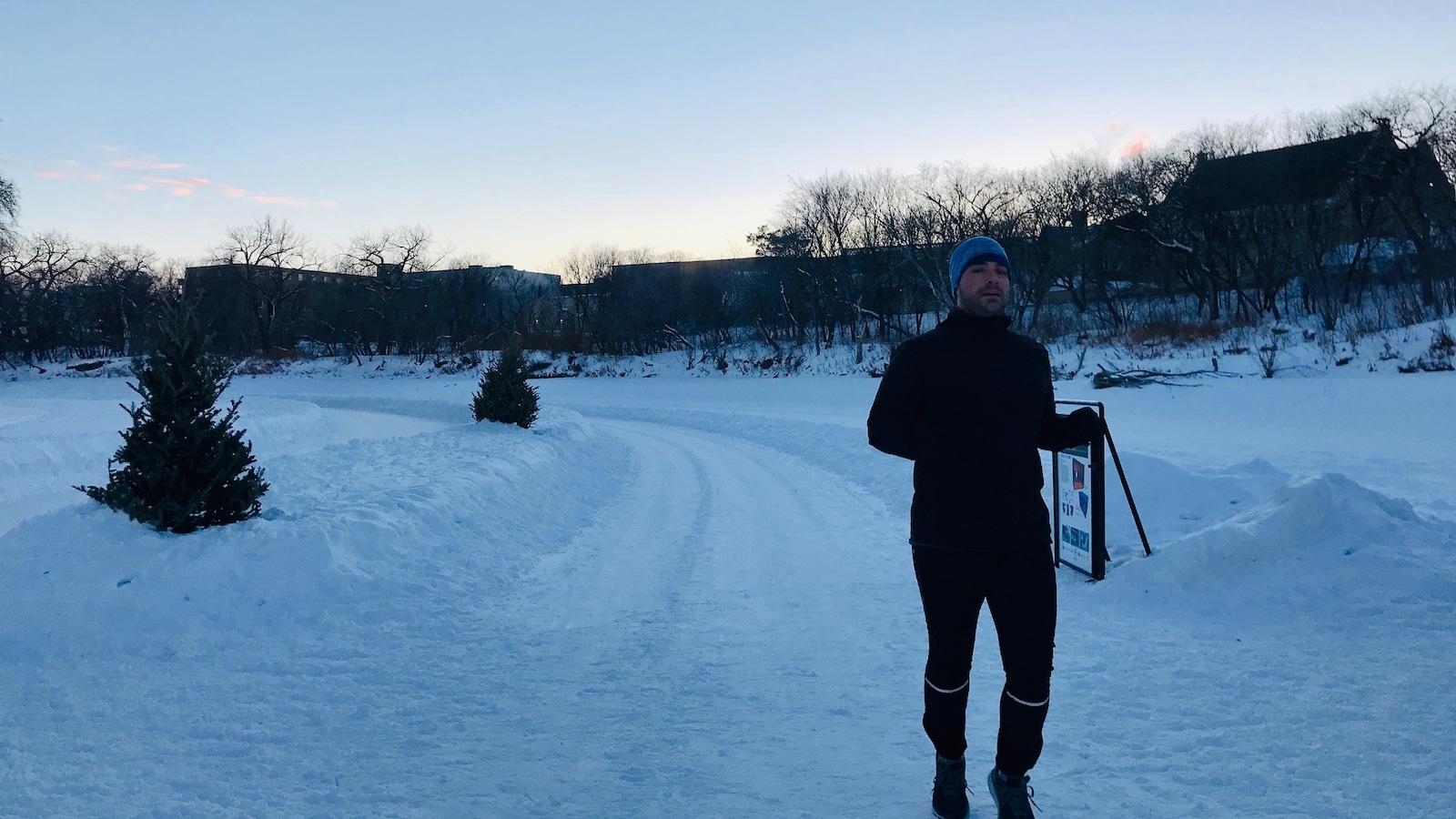 Un homme court dans un sentier enneigé.