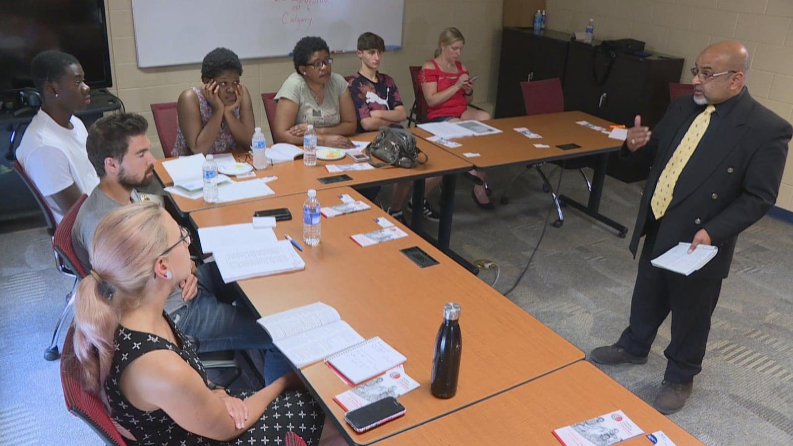 Un homme habillé en costume fait la classe à une dizaine d'élèves - immigrants francophones, assis autour de tables installés en L.