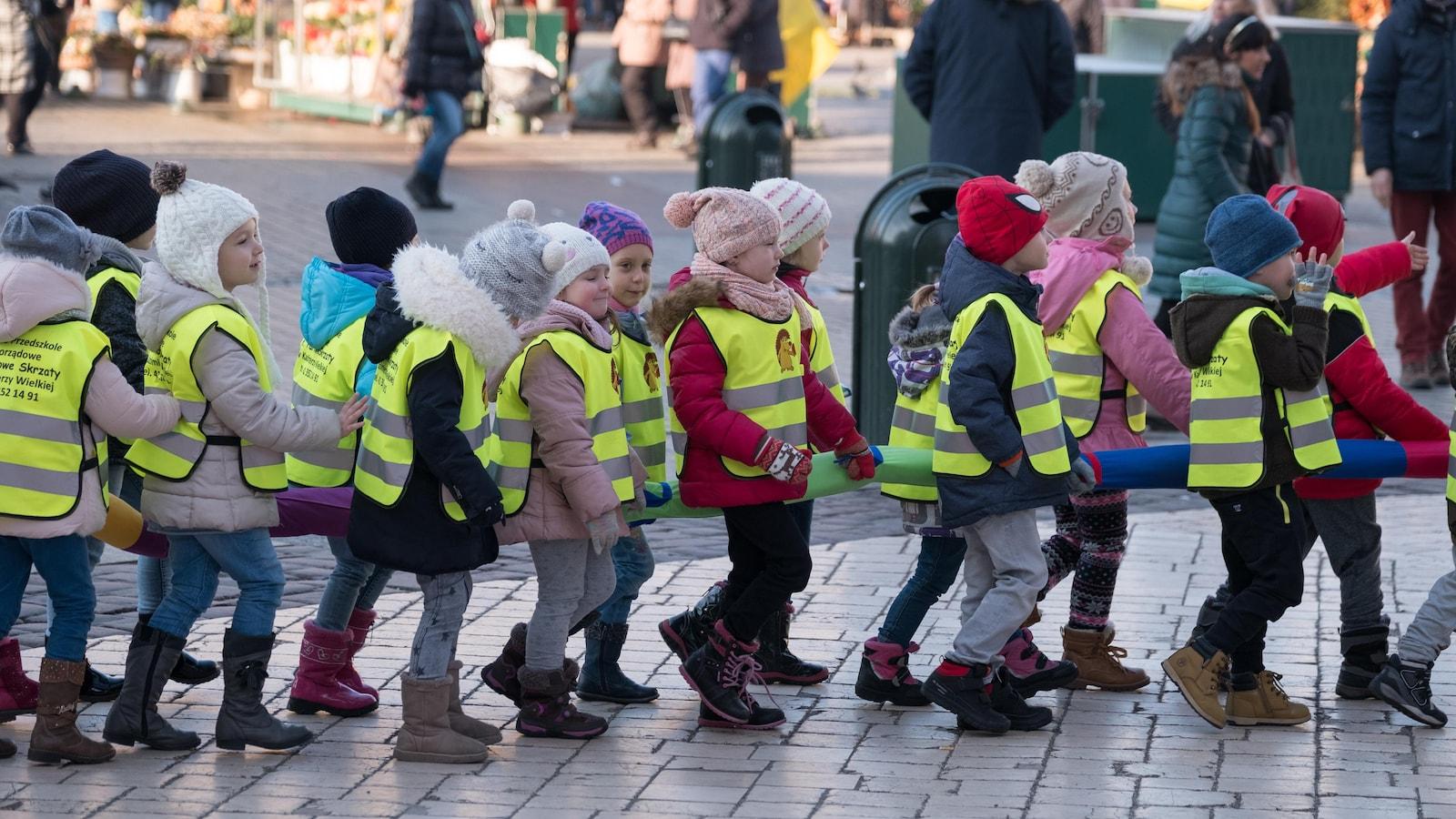 Des enfants vêtus de dossards réfléchissants marchent en file.
