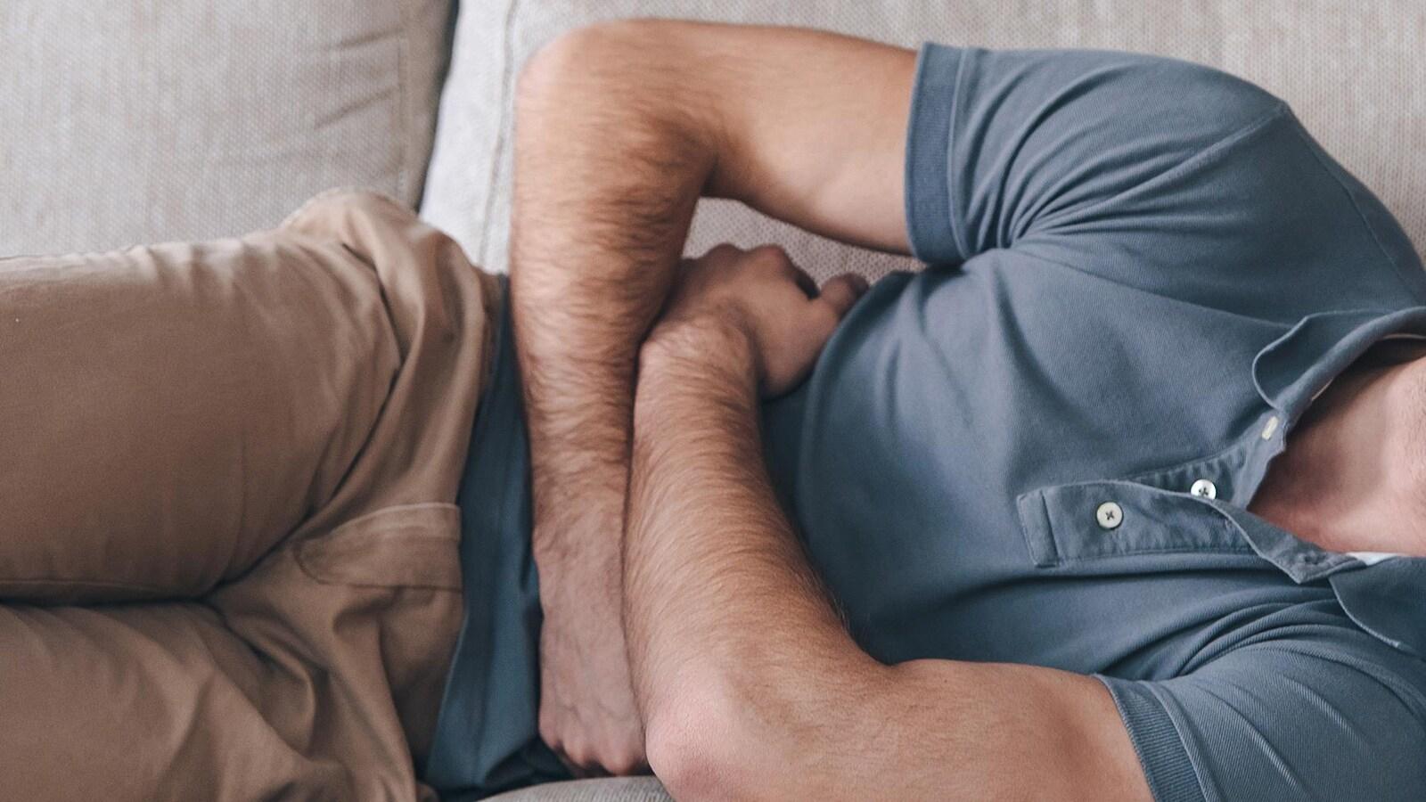 Un homme couché se tient le ventre et semble avoir mal.