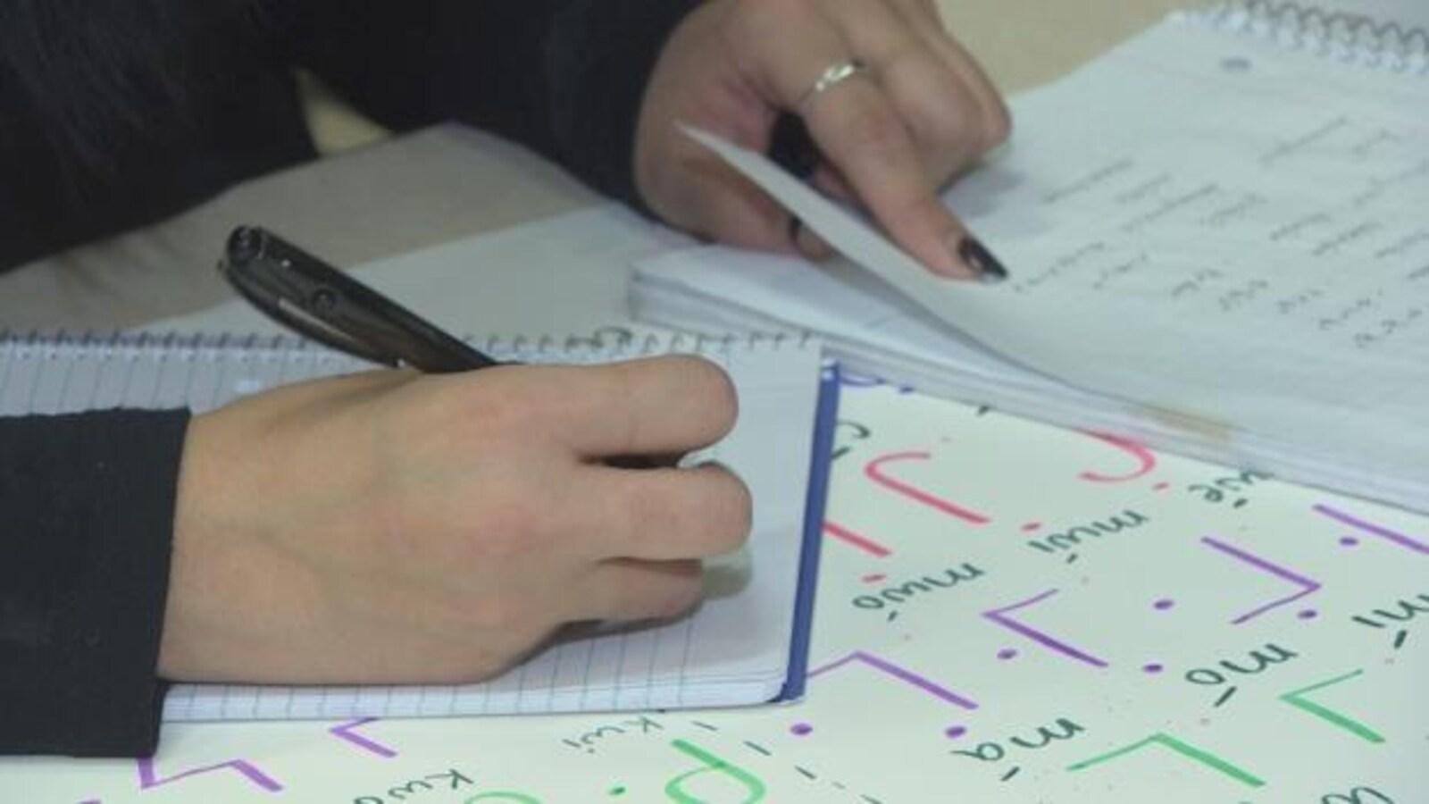 Des mains de femmes écrivent et tournent la page d'un cahier où il y a des lettres cries.