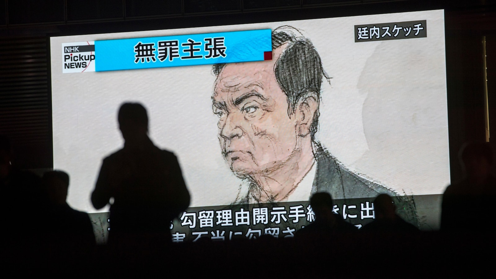 Des passants devant un écran télé sur lequel on peut voir une caricature de Carlos Ghosn lors de son audition par la justice japonaise.