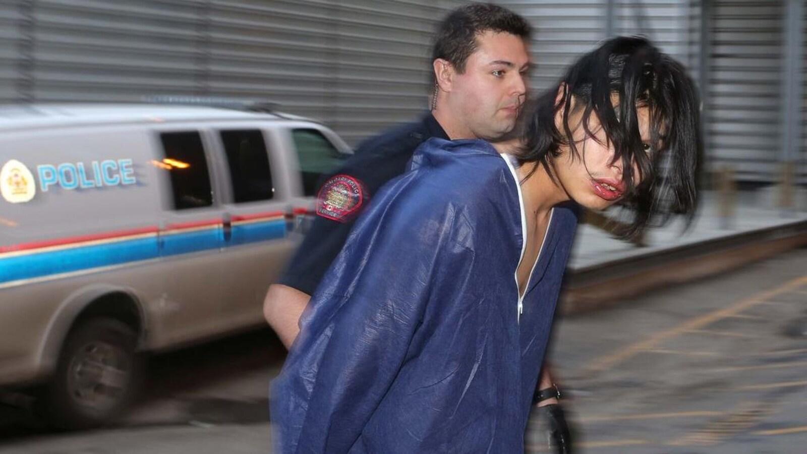 Curtis Healy, vêtu d'un uniforme de prisonnier bleu et le visage partiellement caché par ses cheveux longs, est escorté par un policier.
